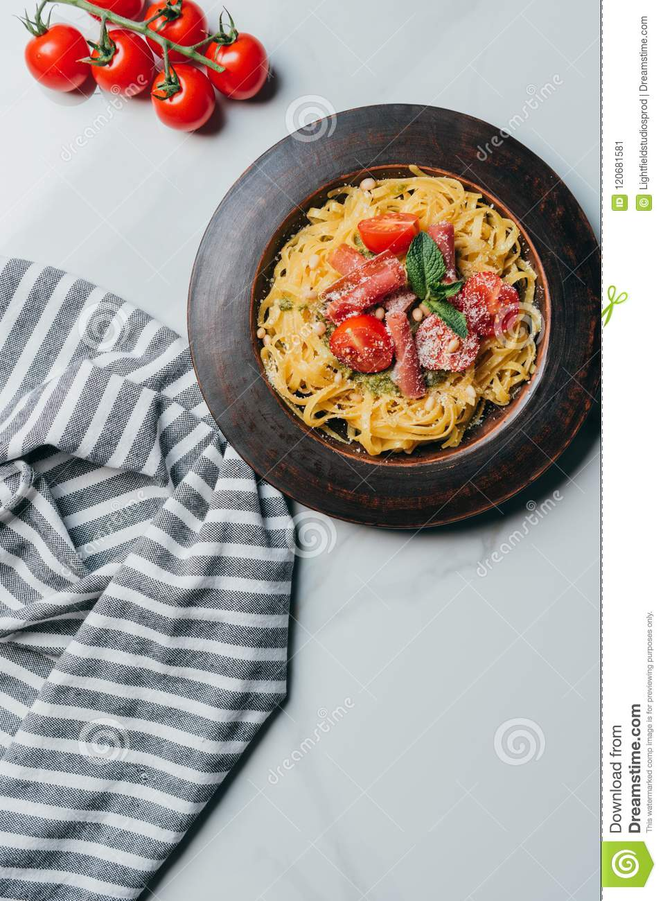 elevated view of pasta with mint leaves, jamon and cherry tomatoes covered by parmesan on plate at marble table