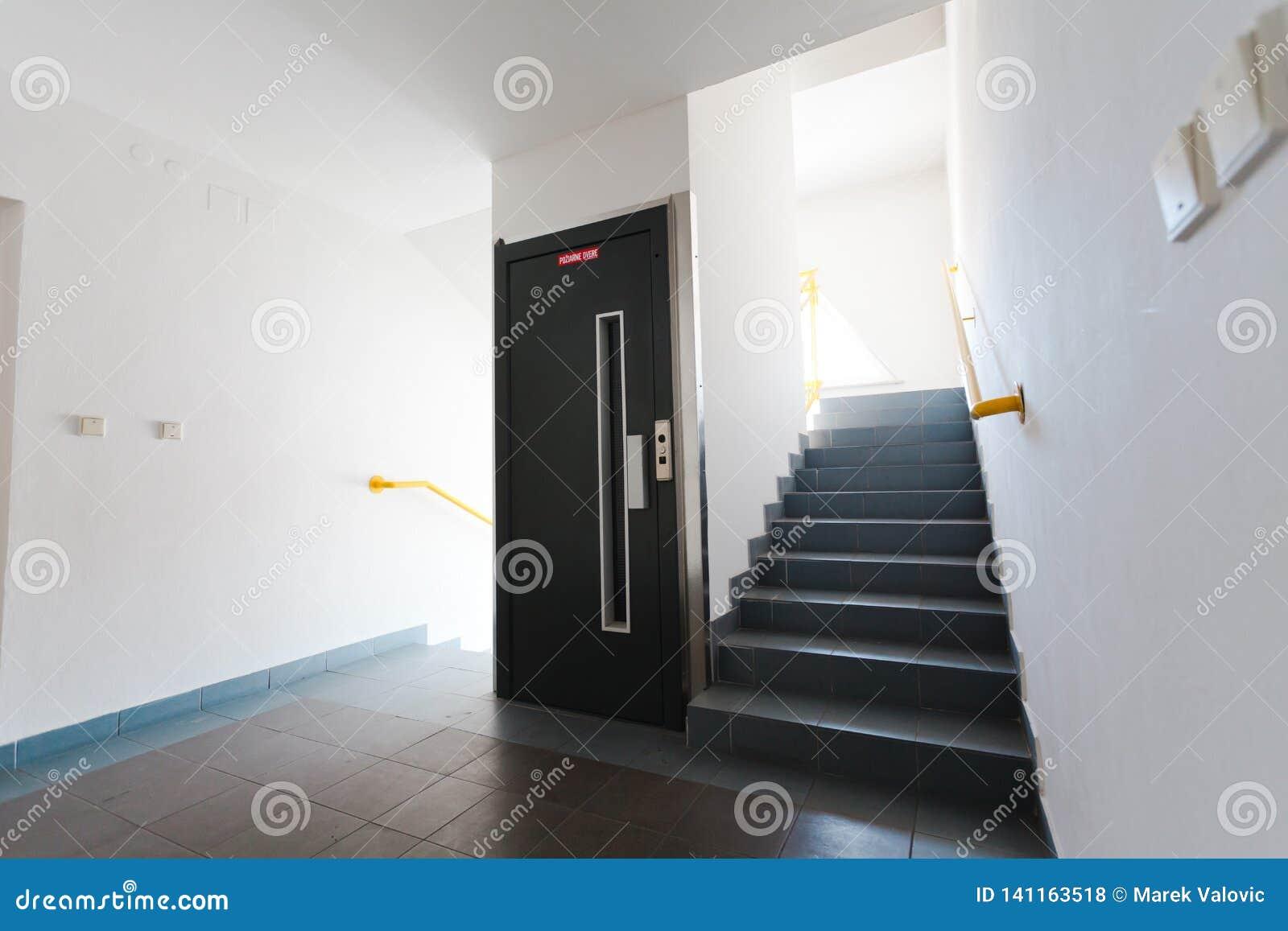 Elevatordörr och trappuppgång - vita väggar och ljust fönster