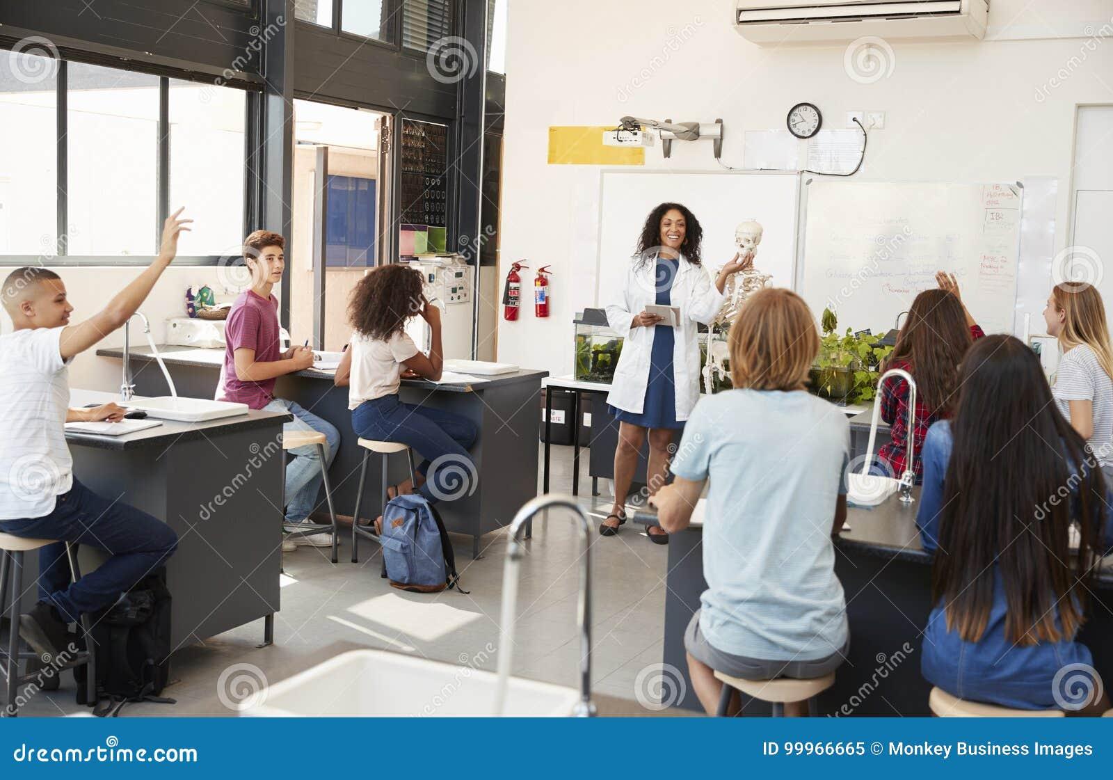 Elever som lyfter händer i en högstadiumvetenskapskurs