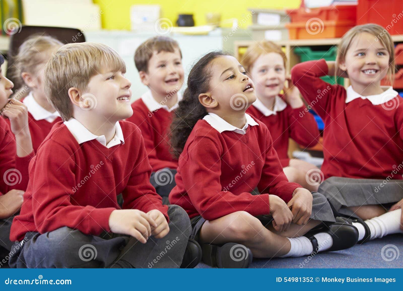 Elever som sitter på Mat Listening To Teacher