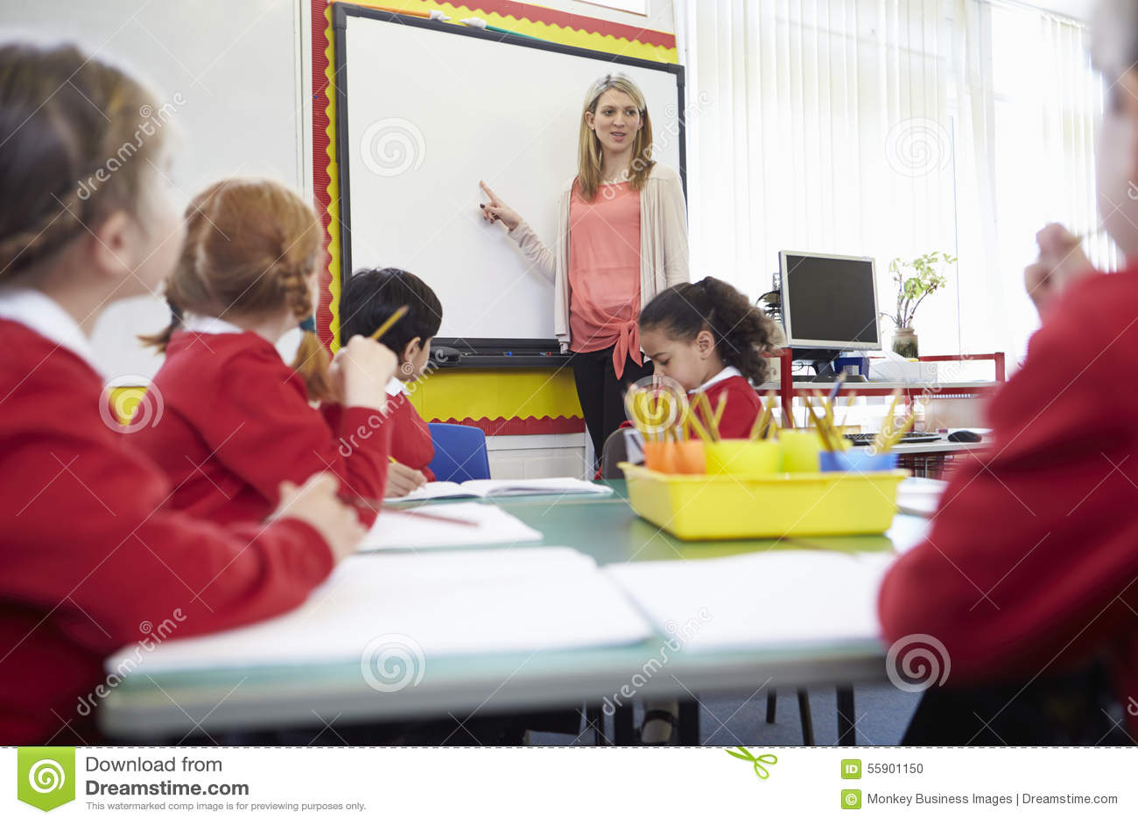 Elever som sitter på tabellen som läraren Stands By Whiteboard