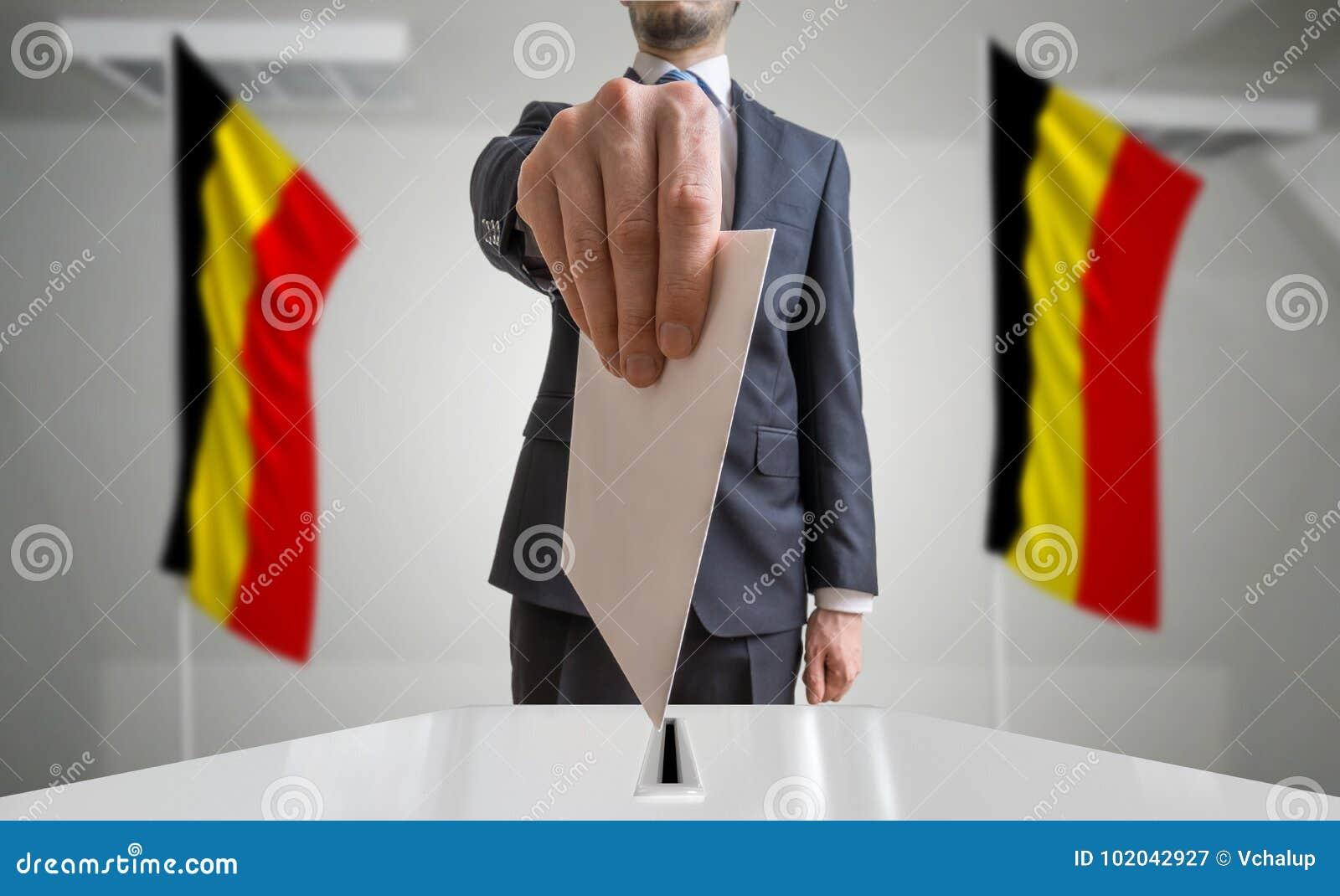 Elezione o referendum nel Belgio L elettore tiene il voto di cui sopra disponibile della busta Bandiere belghe nel fondo