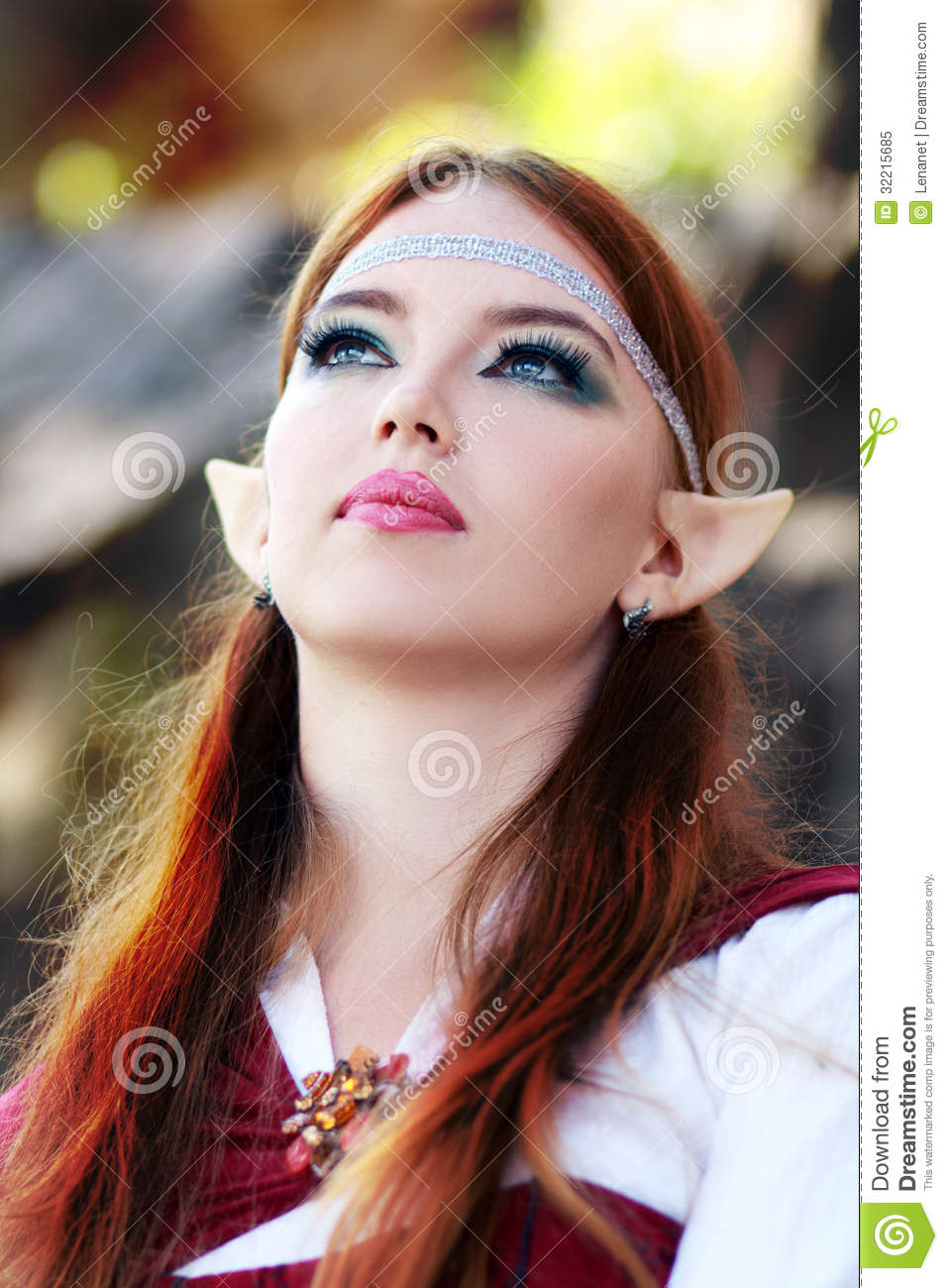 Elf warrior girl on the rock in red cloak posing outdoor close up face ...