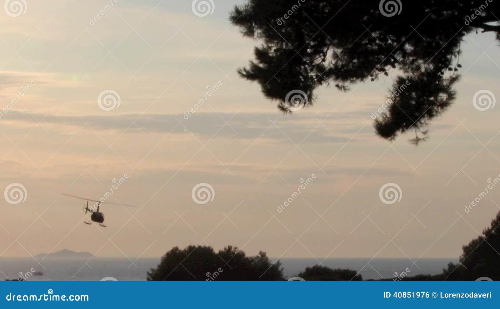 L Elicottero Posizione : Elicottero che vola via nel tramonto su una posizione del mare