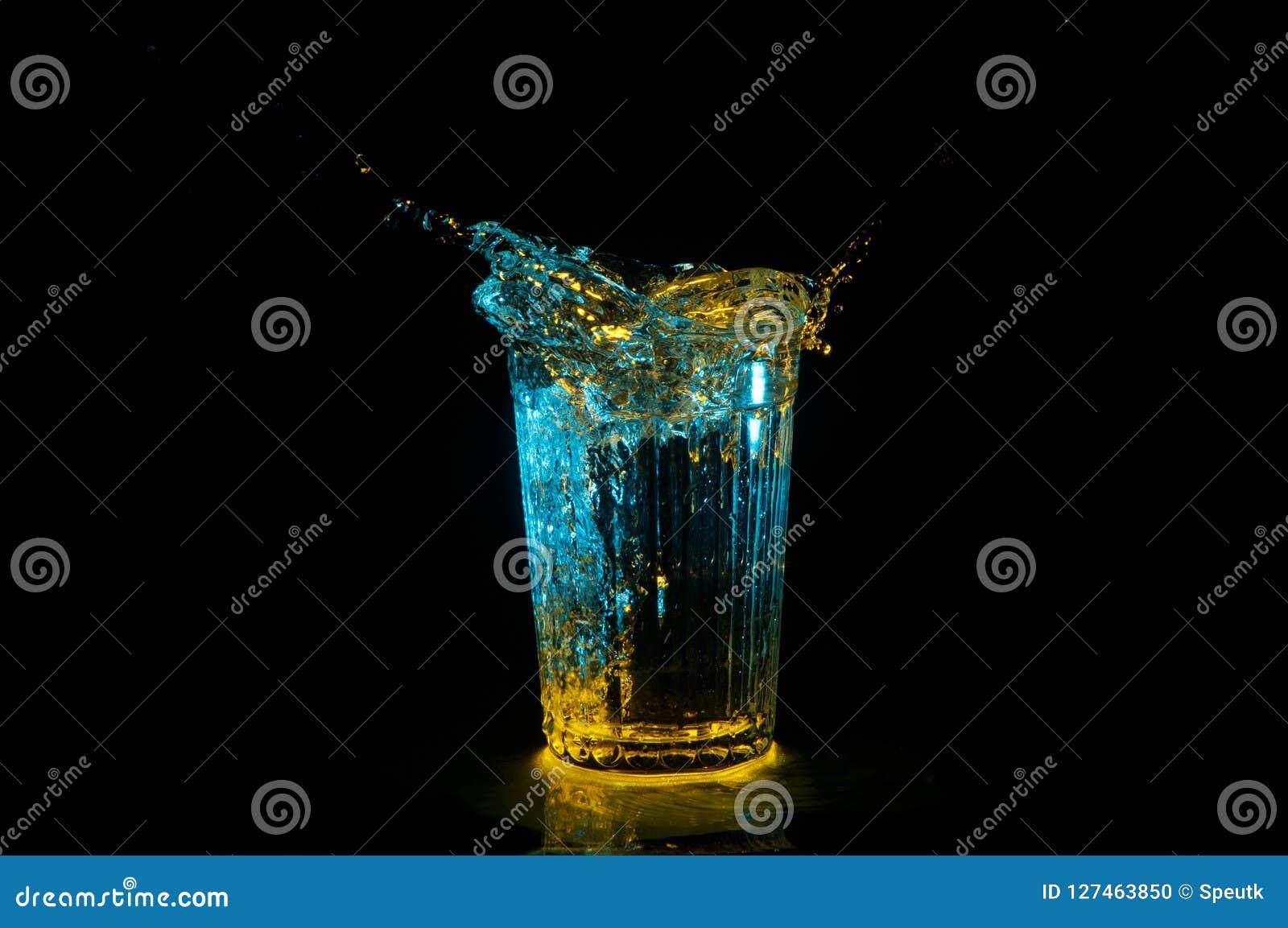 Ellips van water het bespatten uit een geribbeld glas onder gele en blauwe die lichten op een zwarte achtergrond worden geïsoleer