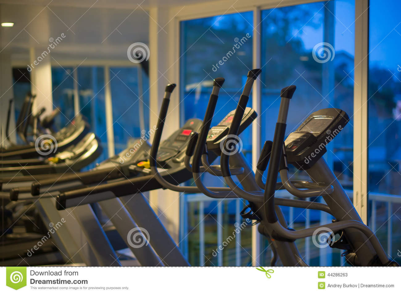 Elliptical cross trainers in a fitness gym at evening