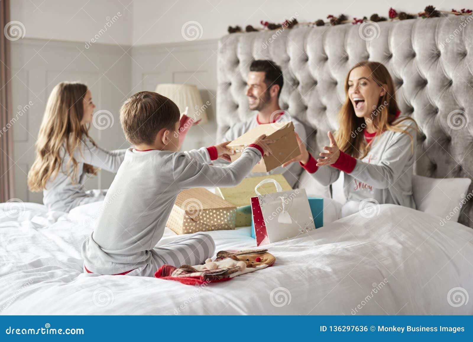 Eltern, die Geschenke von den Kindern wie sie Sit On Bed Exchanging Present am Weihnachtstag öffnen