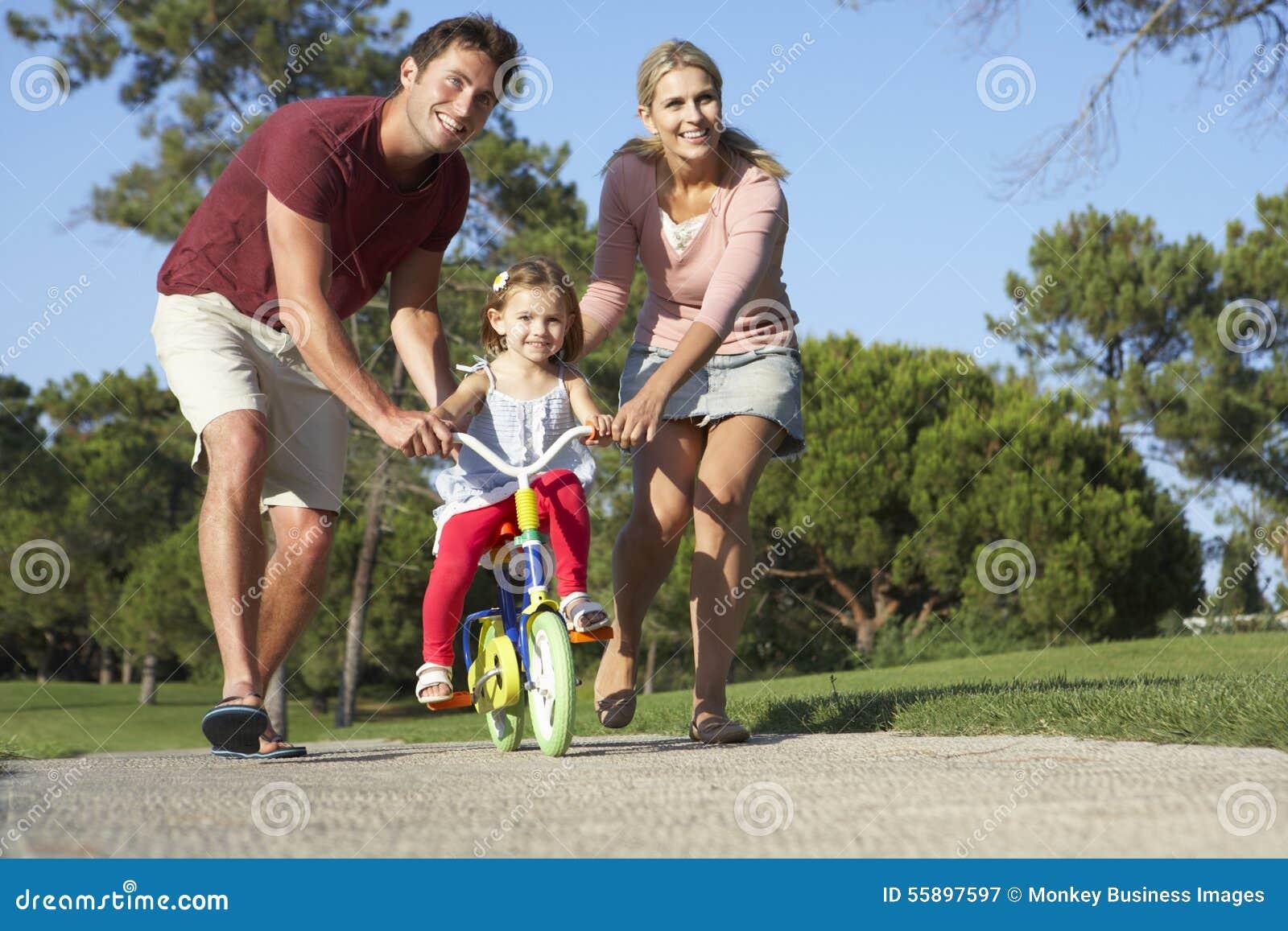 Eltern, die Tochter unterrichten, Fahrrad im Park zu reiten