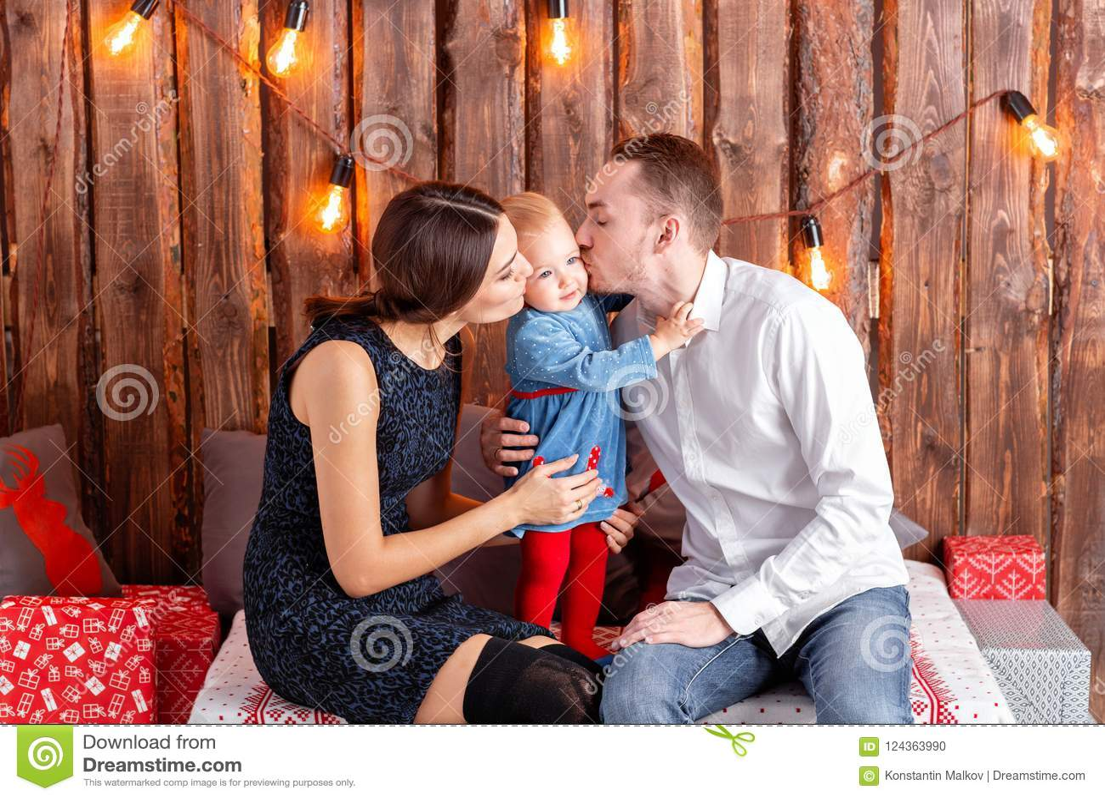 Eltern und Kind, die Spaß im Dachboden-ähnlichen Raum, hölzerner rustikaler Hintergrund mit einer Girlande von Birnen haben Liebe