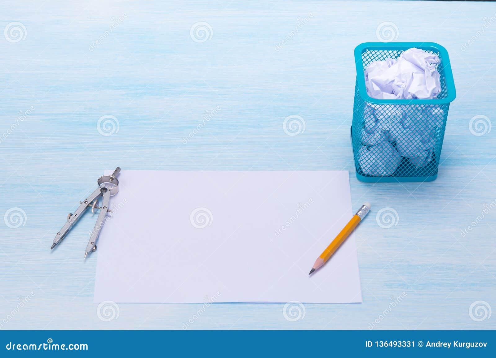 Em um fundo claro, em objetos do escritório, no assunto para esboçar, em um lápis e em um balde do lixo