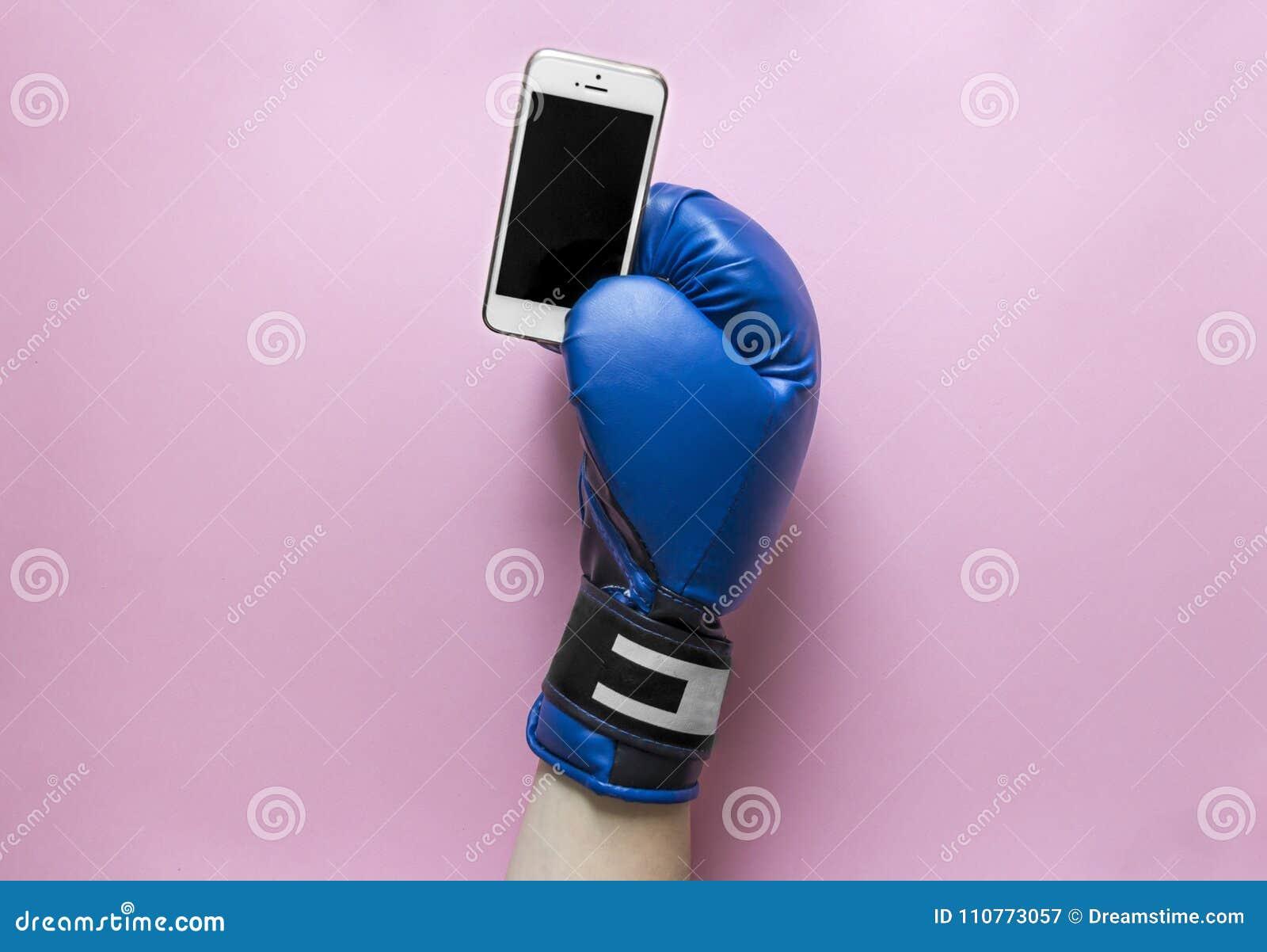 Em um fundo cor-de-rosa uma mão em uma luva de encaixotamento da cor azul com um telefone nas mãos