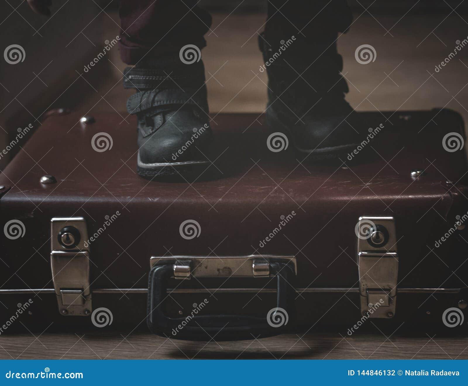 Em uma mala de viagem retro do marrom de Borgonha do vintage s?o os p?s de uma crian?a nas sapatas Baixa chave Sombras do res?duo