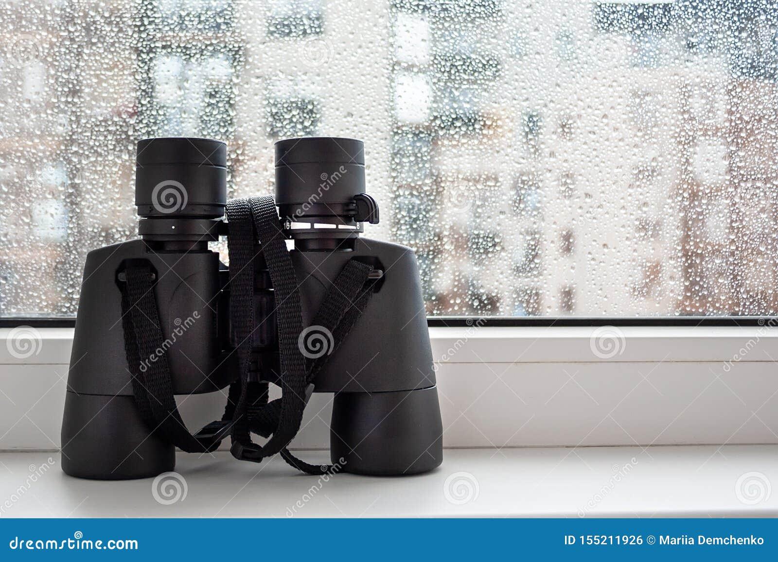Em uma soleira branca pela janela com os pingos de chuva no vidro são os binóculos pretos para observar vizinhos