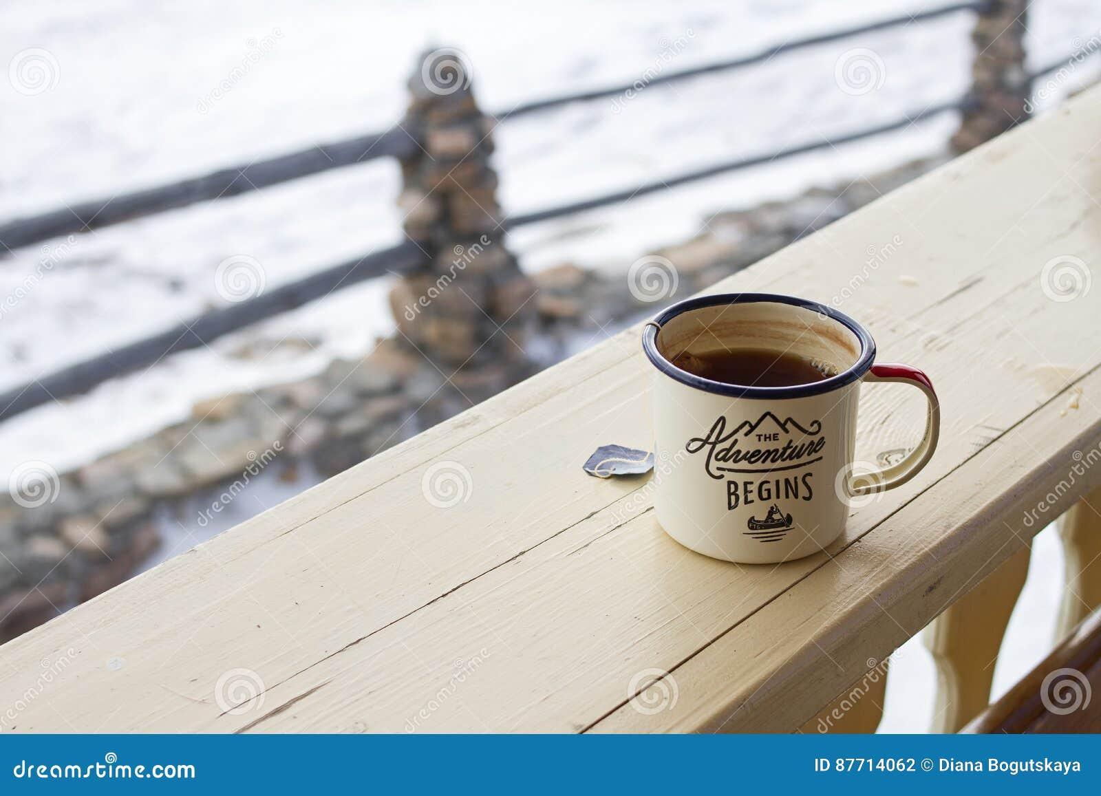 Emalj rånar med den starka te och tepåsen på ett trästaket på en snöig naturlig bakgrund