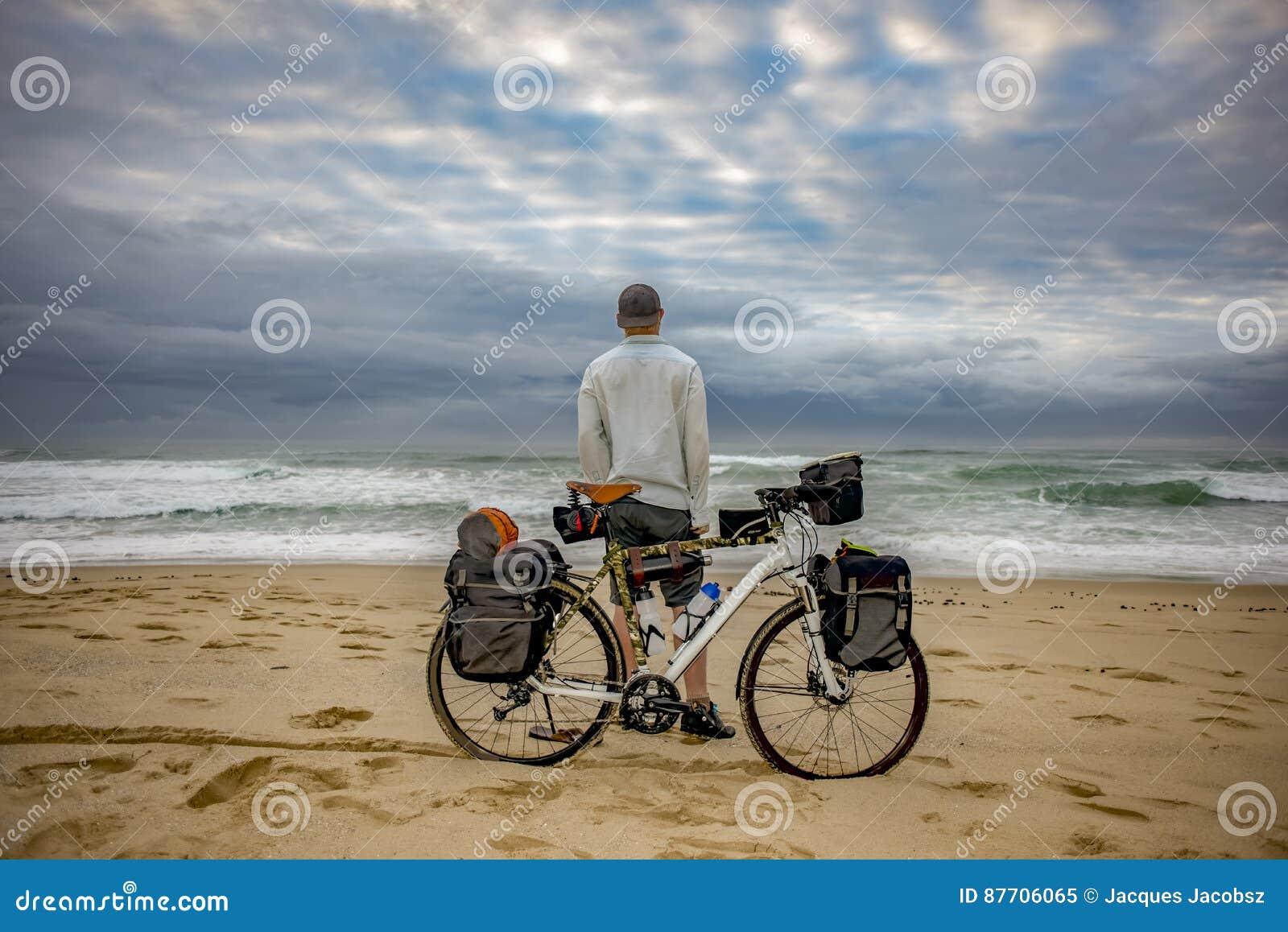 Emballeur de cycle avec la bicyclette sur la plage