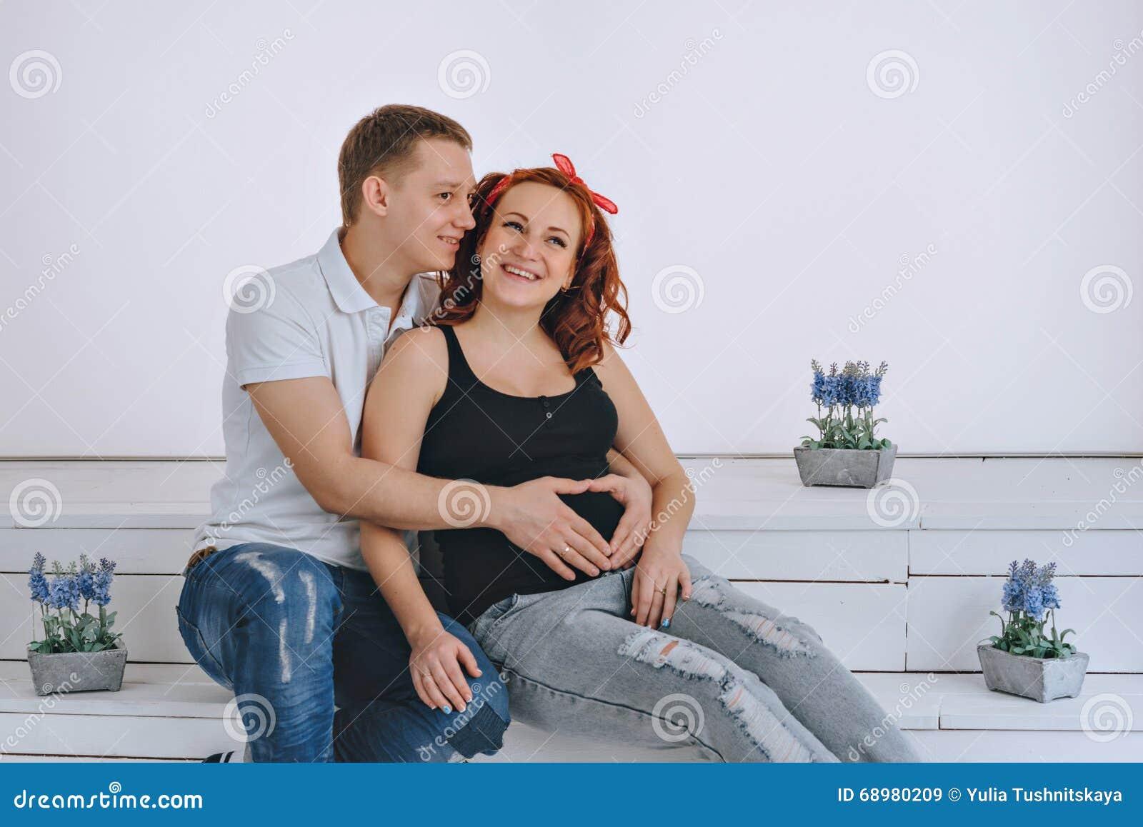 Embarazo El vientre de una muchacha embarazada y de su marido El marido guarda su mano en la esposa del vientre Padres futuros