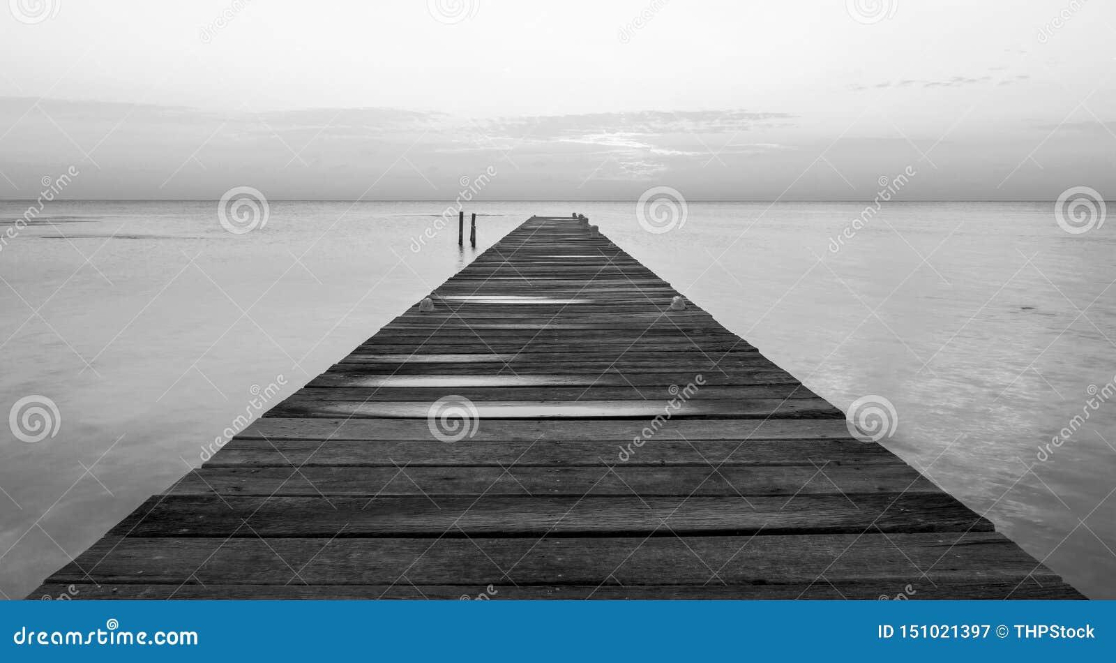 Embarcadero de madera en Dawn Black y el blanco