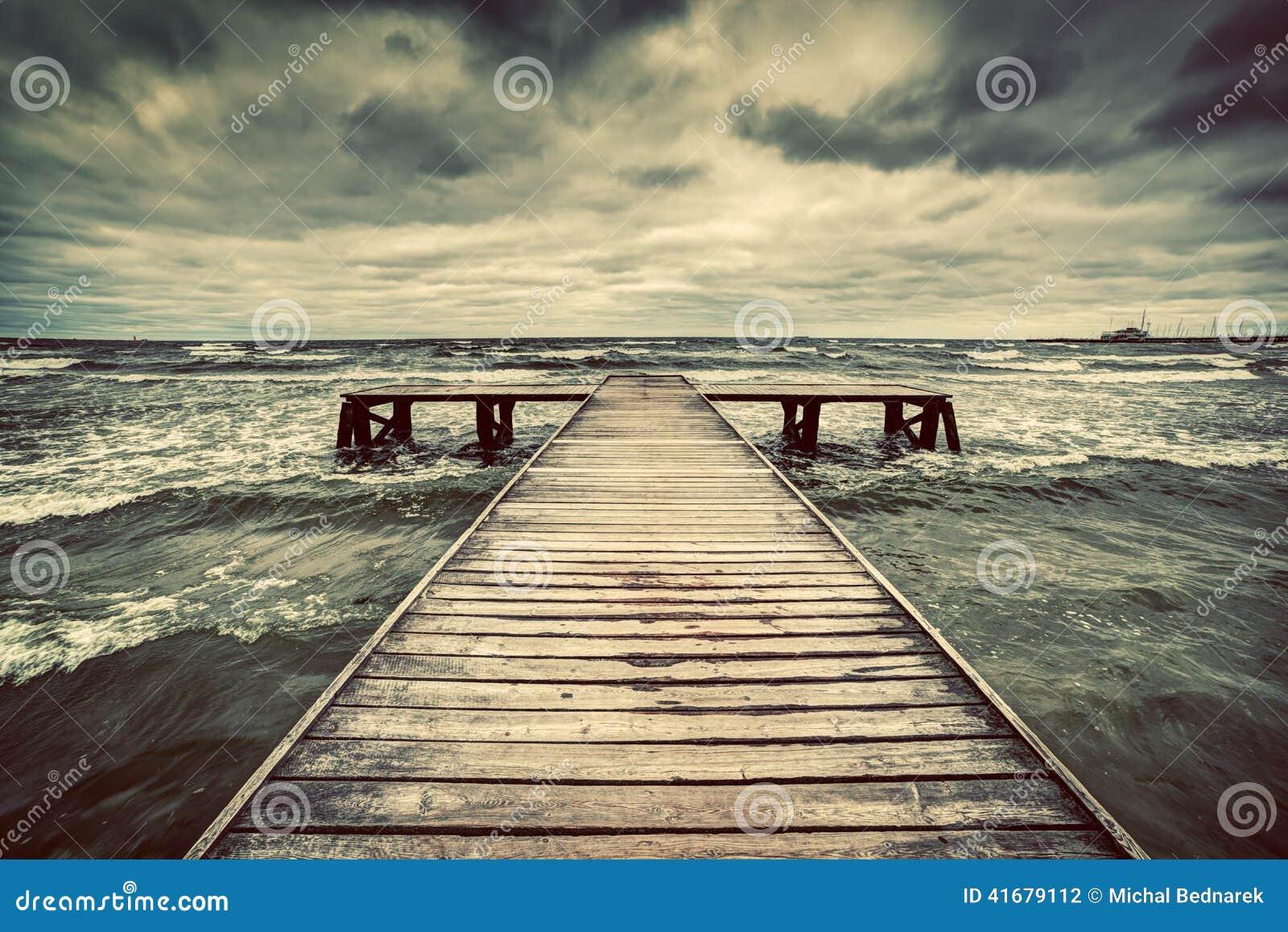 Embarcadero de madera viejo durante tormenta en el mar Cielo dramático con las nubes oscuras, pesadas