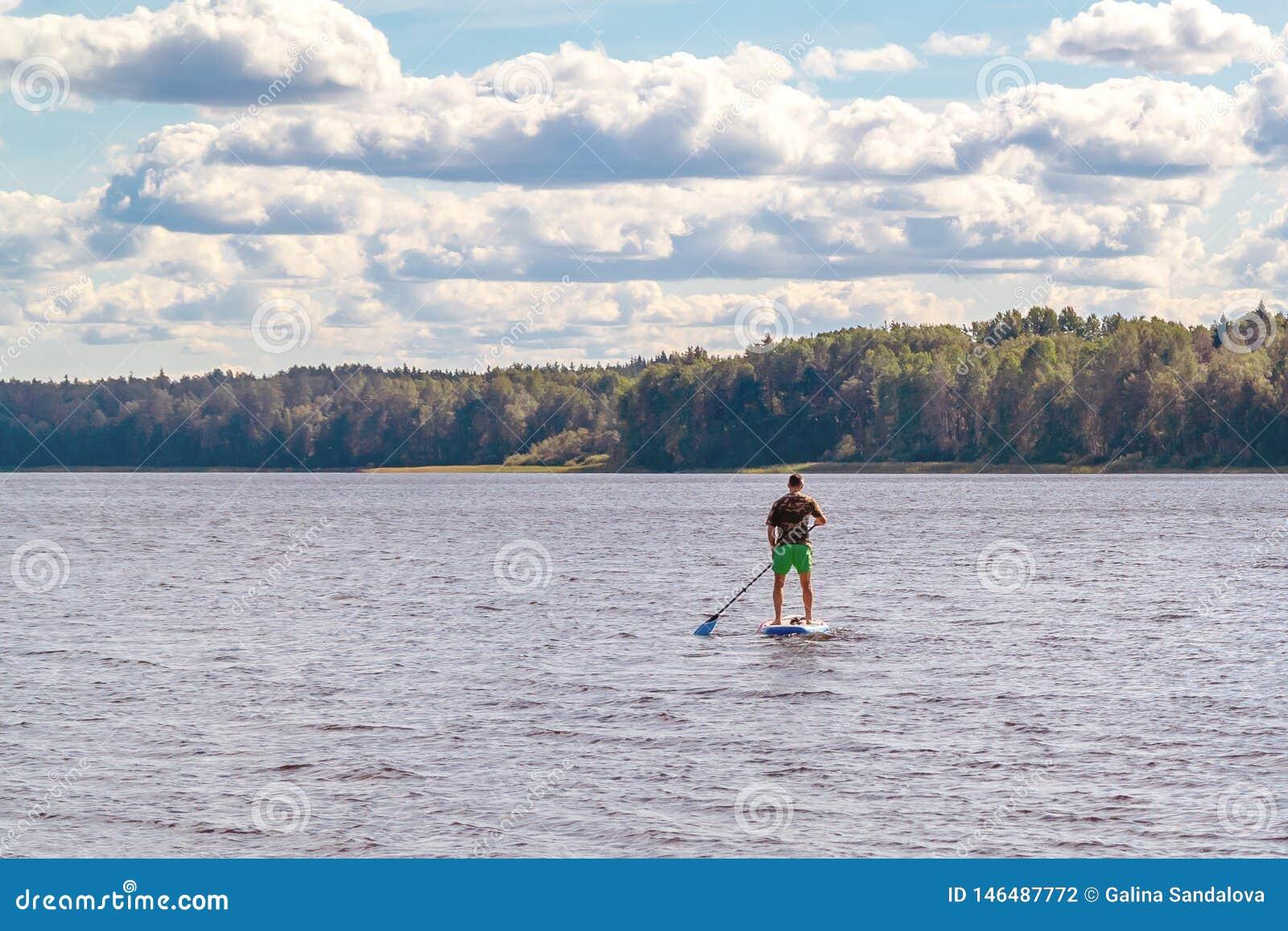 Embarque standup da p? do homem Imagem do SUP do homem novo que surfa no lago