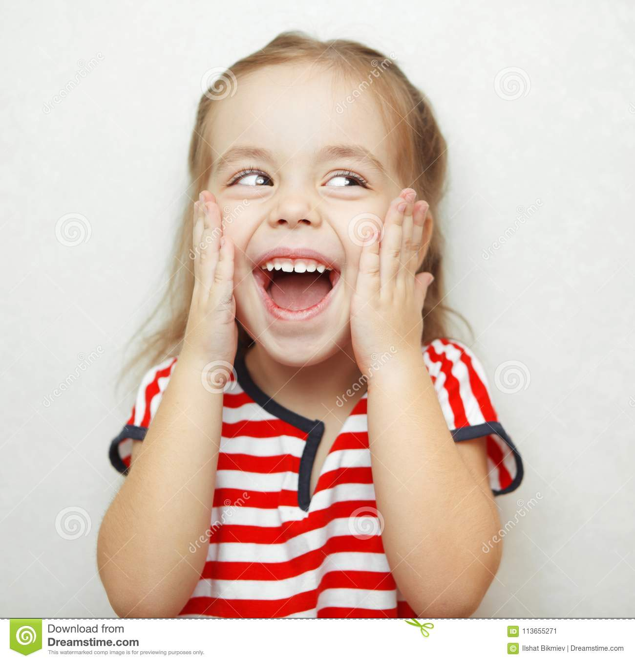 39c6a29a867f Embarrassed little girl with broad smile thouches her cheeks with hands,  looks sideways dressed in striped T-shirt and stands beside white wall.  Portrait ...