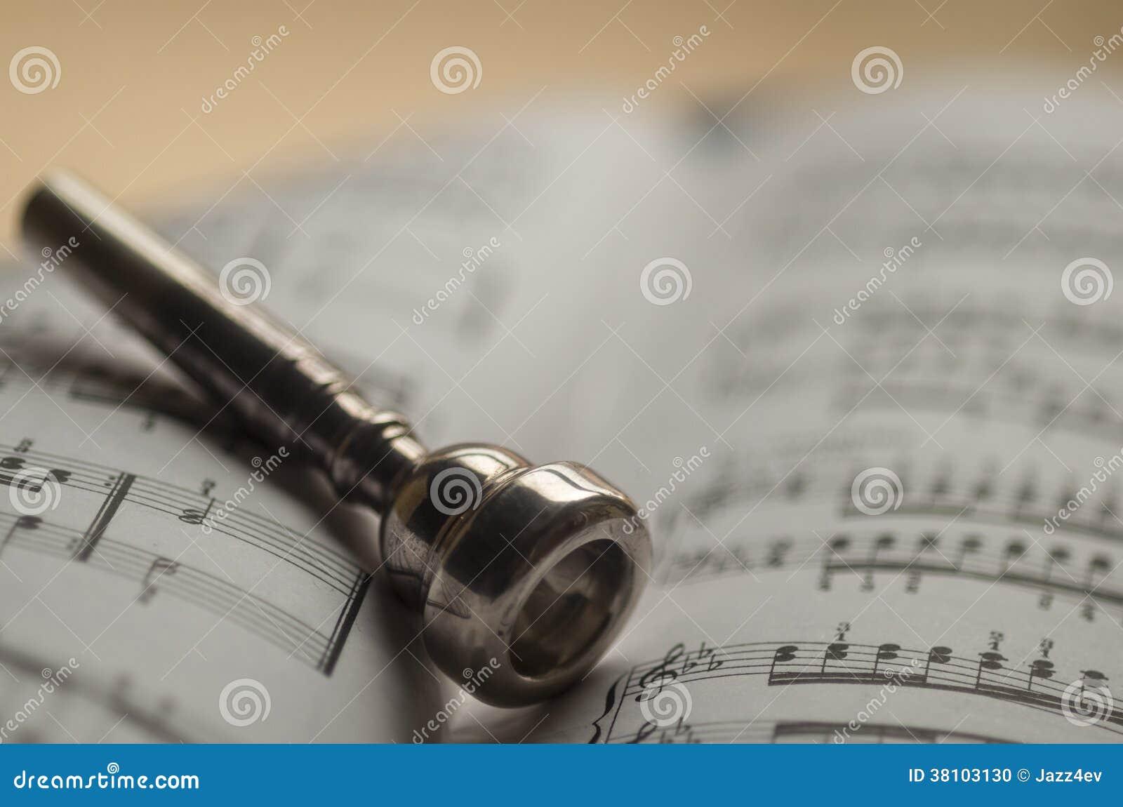 Embouchure de trompette sur le cahier de musique de feuille