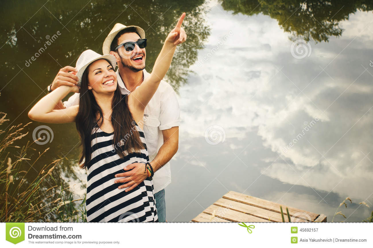 Embrace of happy romantic couple on pier explore the world of be