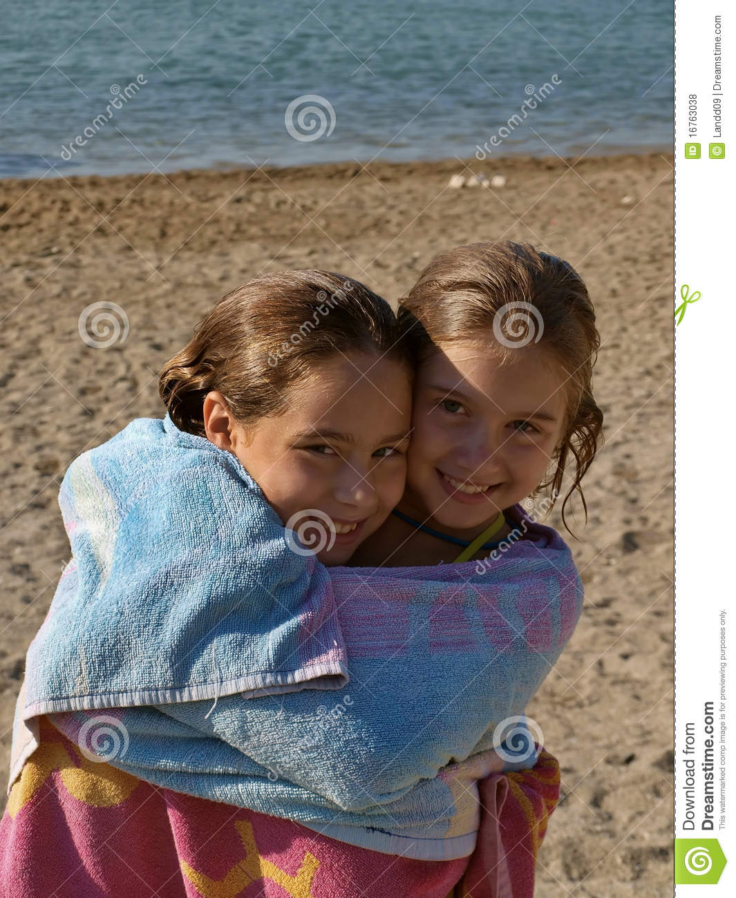 Embraced sisters on beach stock photo. Image of both ...