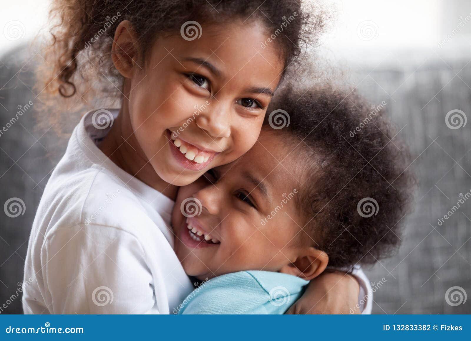 Embrassement heureux d enfants de mêmes parents d Afro-américain, se reposant ensemble