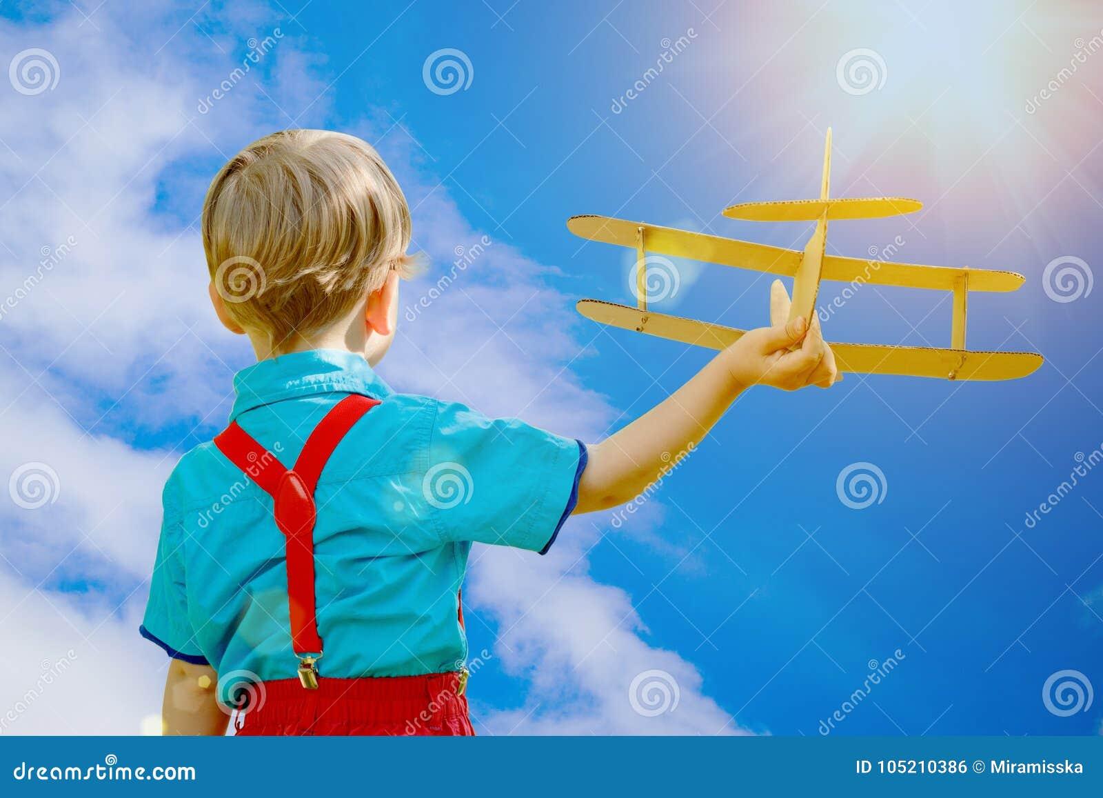 Embroma fantasía Niño que juega con el aeroplano del juguete contra el cielo y el cl