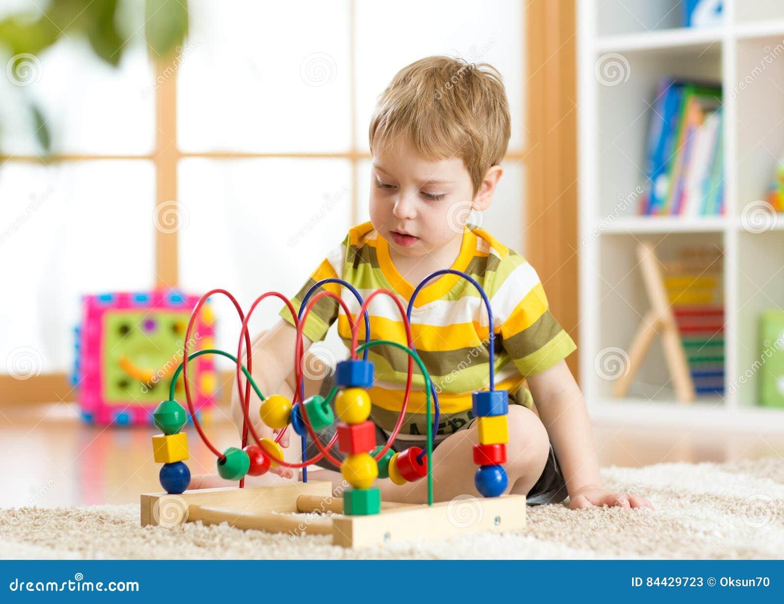 Embrome los juegos del muchacho con un juguete lógico multicolor en cuarto de niños