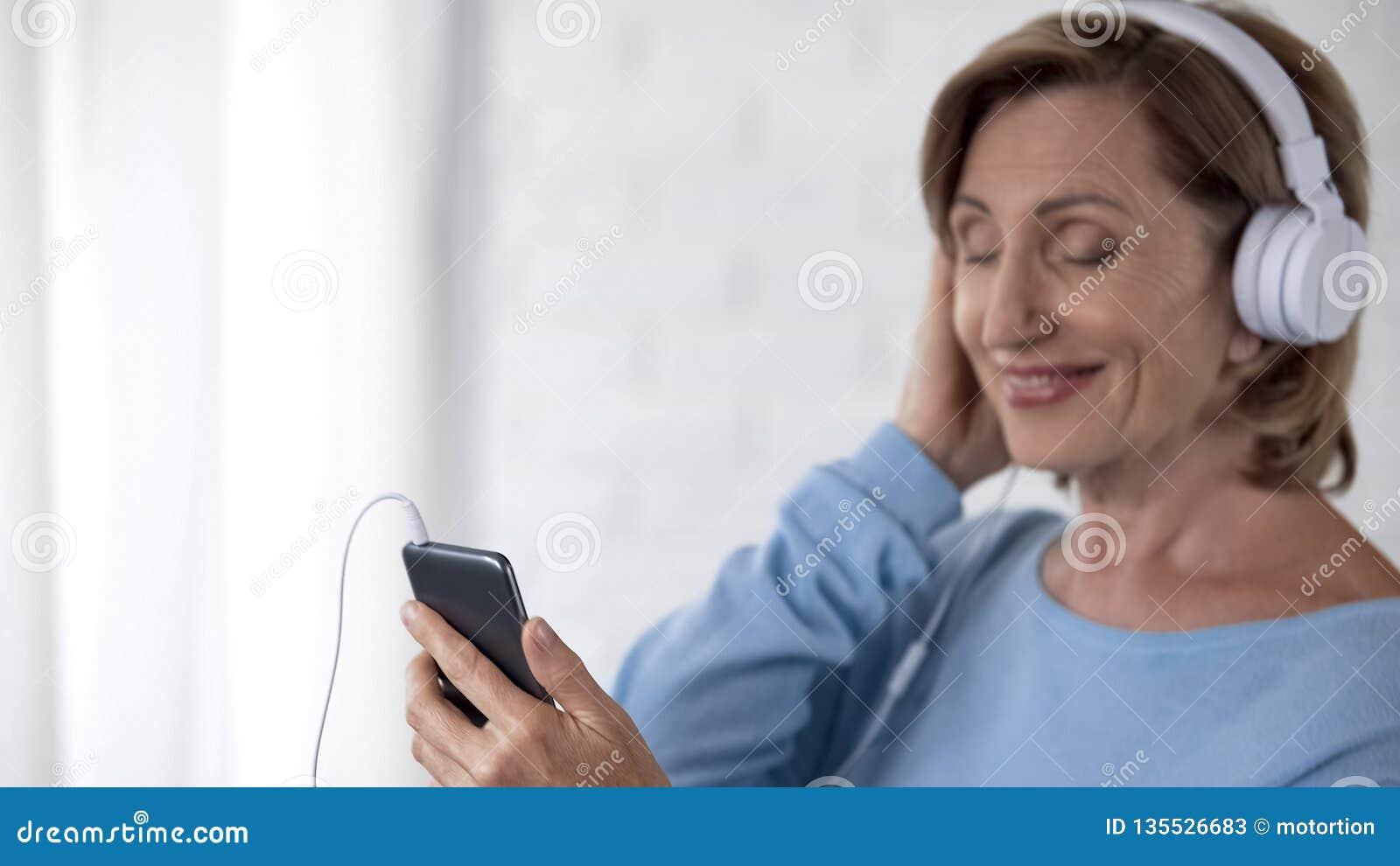 Emeryt dama słucha muzyka na telefonie komórkowym i ono uśmiecha się w hełmofonach