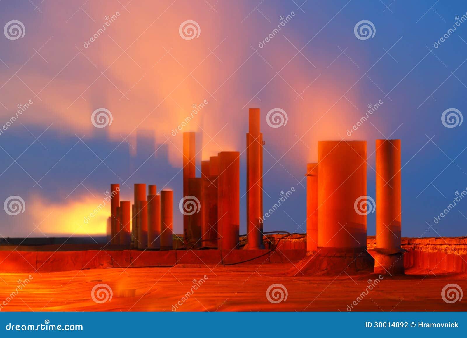 Tubi di fumo della fabbrica con illuminazione di notte fotografia