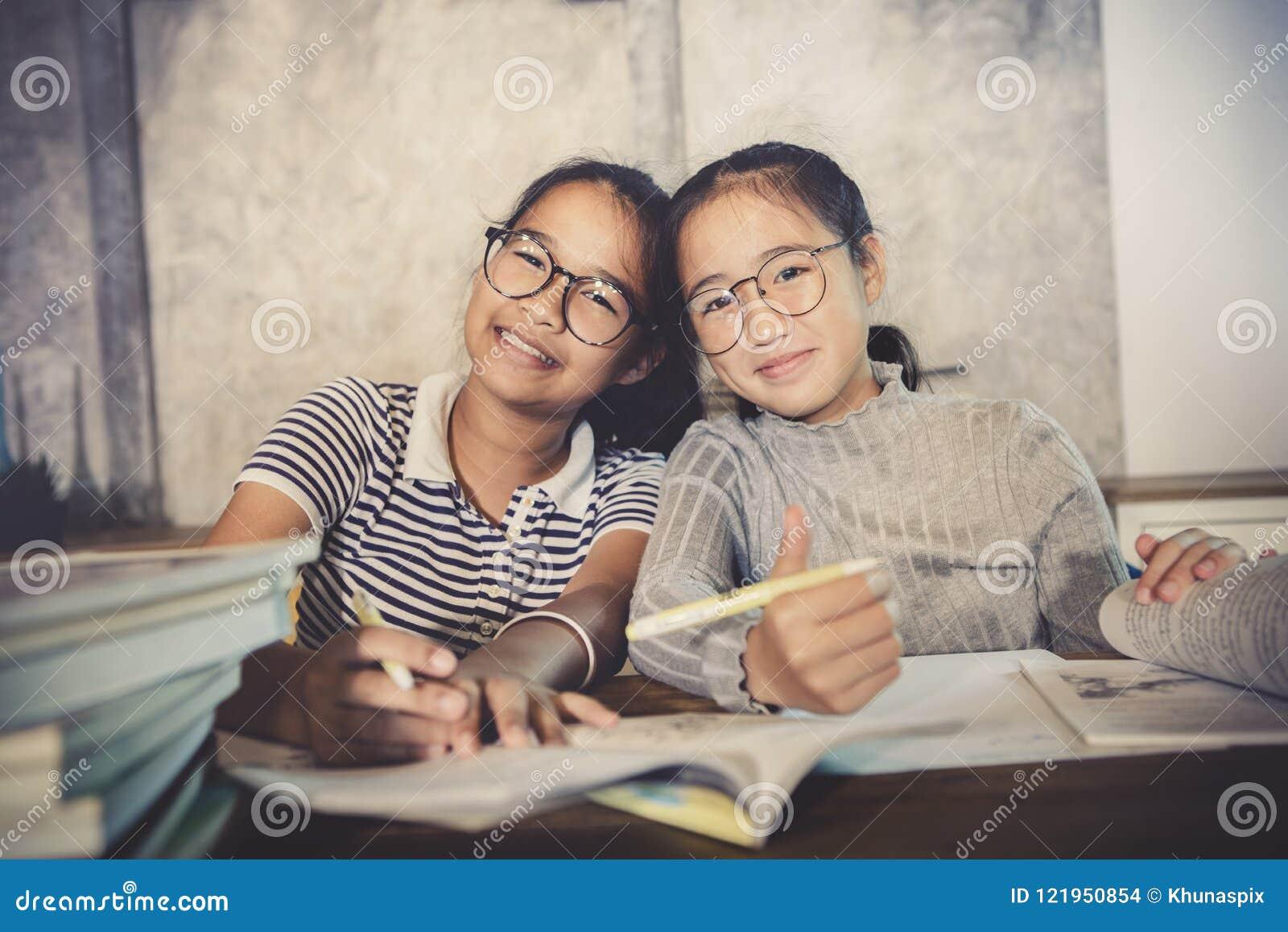 Emoção asiática da felicidade do adolescente que faz o trabalho da casa da escola