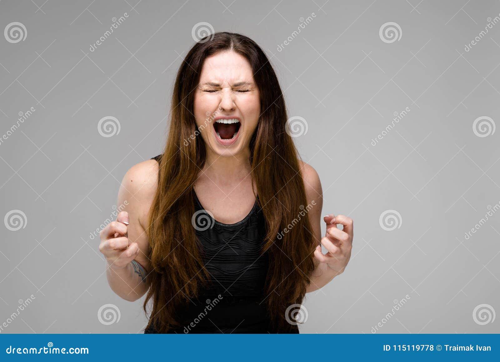 Emocional mais a posição modelo do tamanho no estúdio com a boca aberta que grita mostrando a raiva da agressão queira riscar