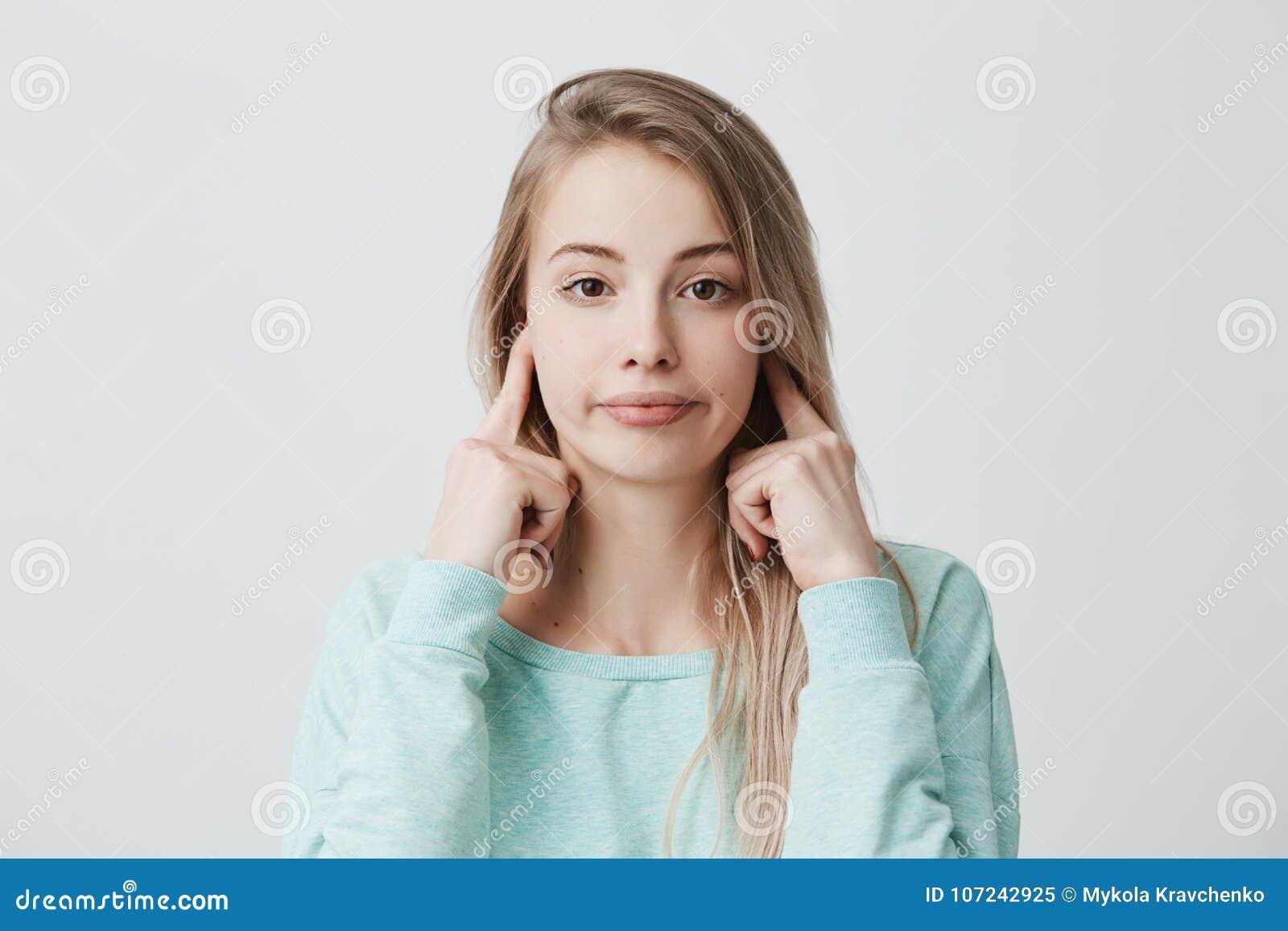 Emociones, reacción y actitud humanas negativas Frustrated molestó a la muchacha con el pelo teñido blonde que tapaba los oídos c