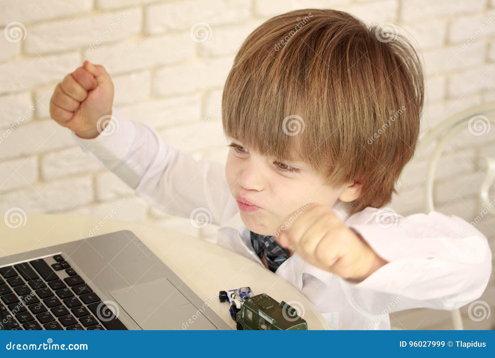 Emocjonalna chłopiec używa laptop