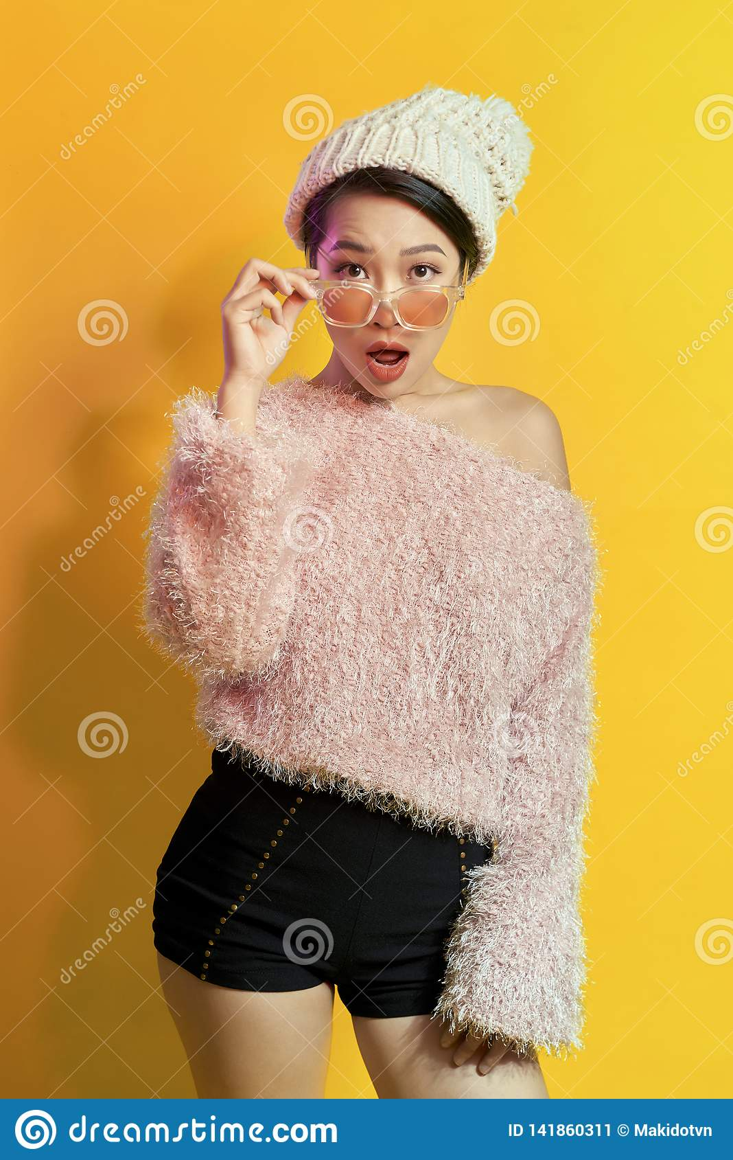 Emotional asian girl with colorful makeup posing on yellow background with eyeglasses. Indoor photo of amazed woman in trendy fur