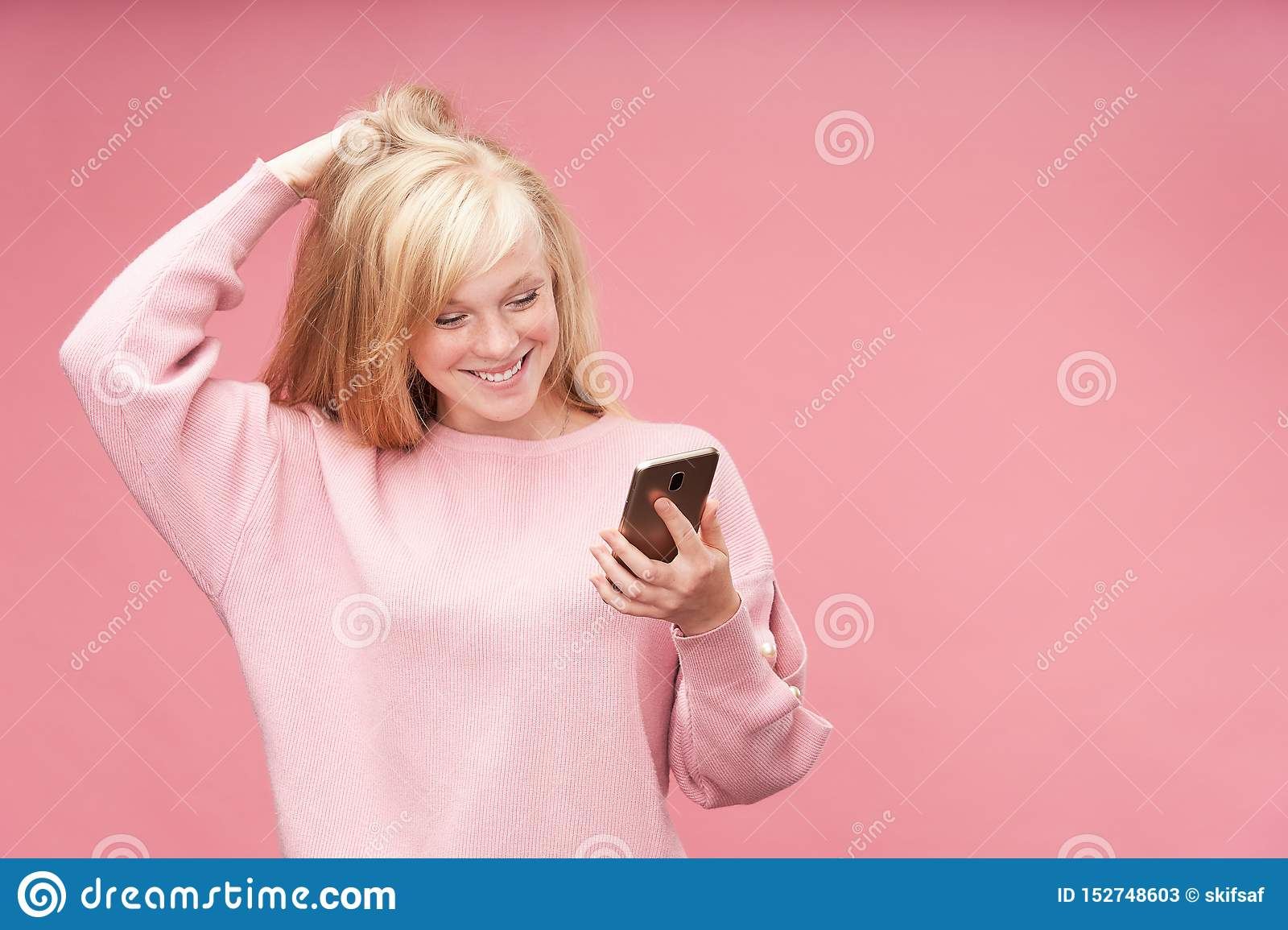 Emotional girl looking at the phone. Young beautiful blonde looks admiringly at the smartphone holding his hand to his head. happy