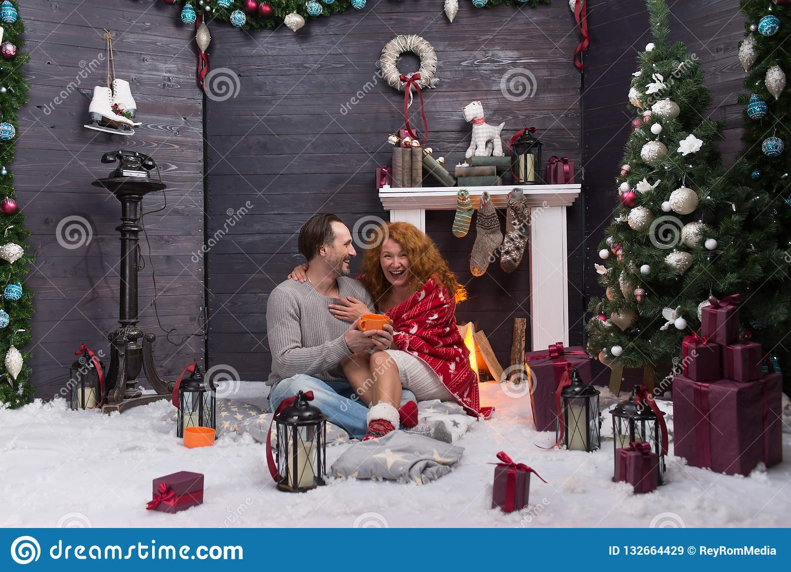 Two romantic people laughing while celebrating New Year near the fireplace
