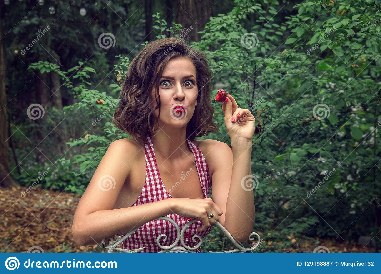 Pin-up girl eats red strawberry. On the face there is an emotionally displayed delight and pleasure