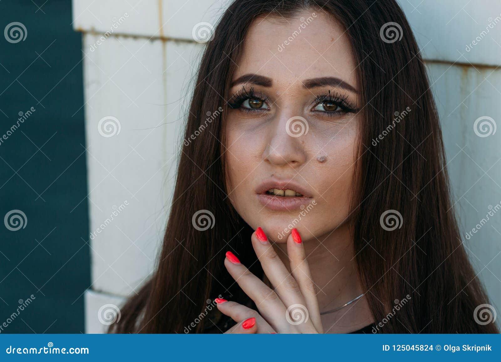 Emotional portrait of Fashion stylish portrait of pretty young woman. city portrait. sad girl. brunette in a black dress. expectat