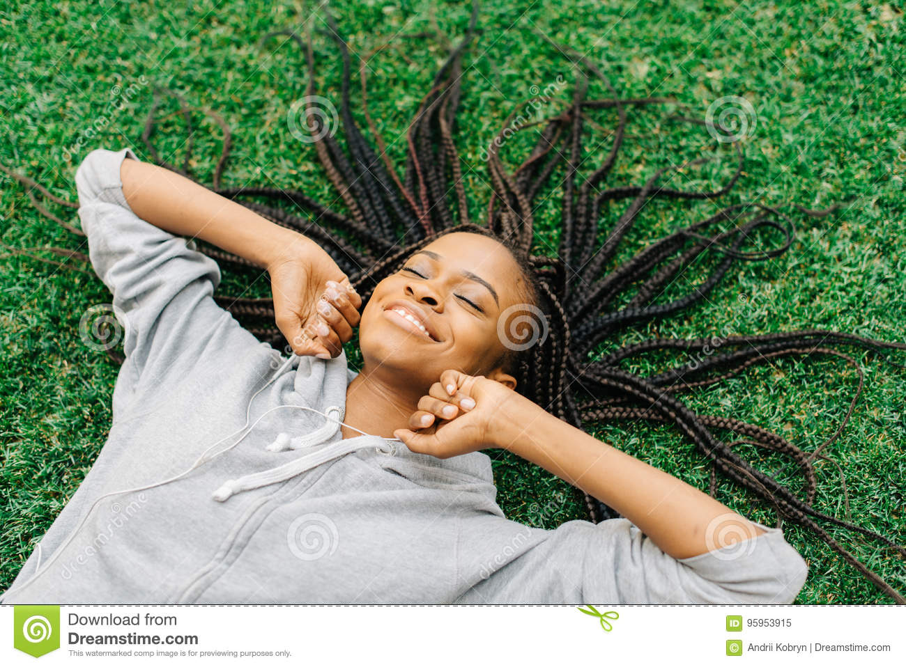 Emotional portrait of the joyful afro-american woman moving hands while laying on the grass and listening to music.