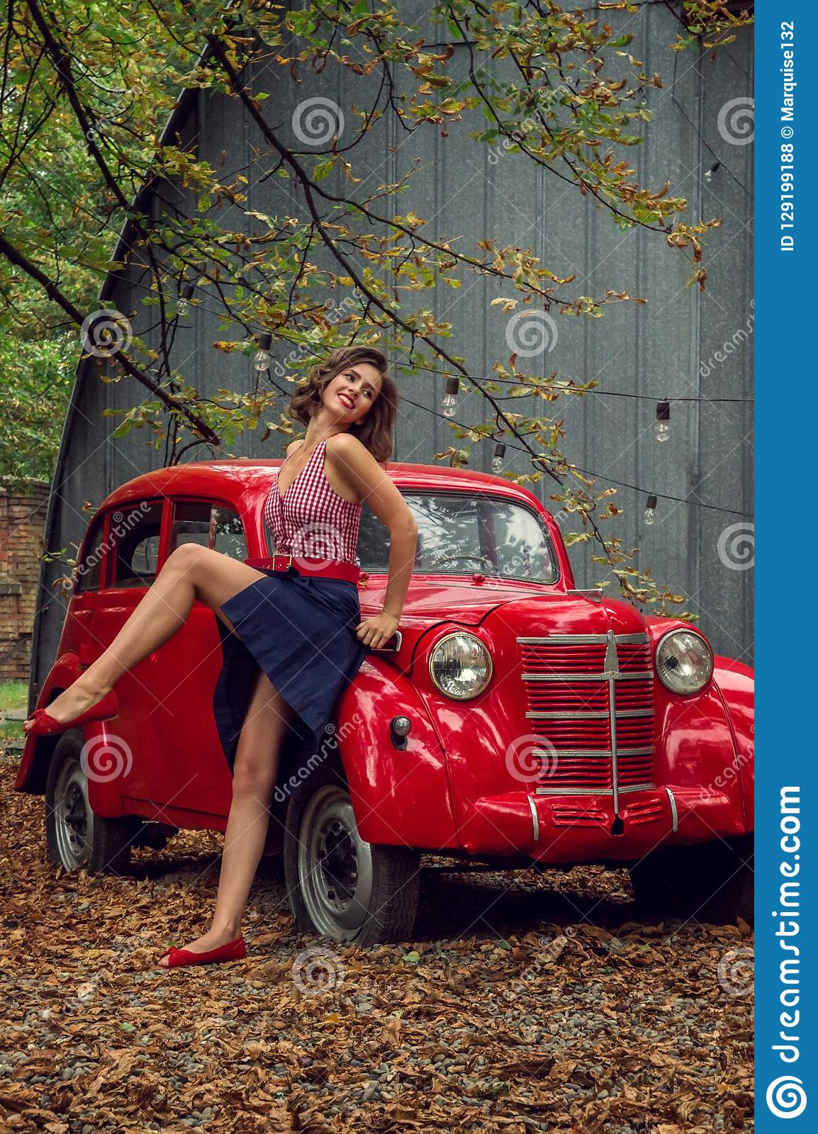 Emotional portrait. Pin-up girl posing near by a red russian retro car.The model laughs loudly, flirtatiously showing slender legs