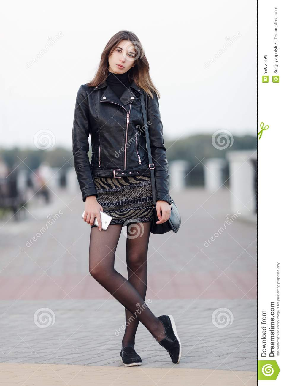 Emotional portrait of a young pretty brunette woman posing full length outdoors city park wearing black leather coat holding smart