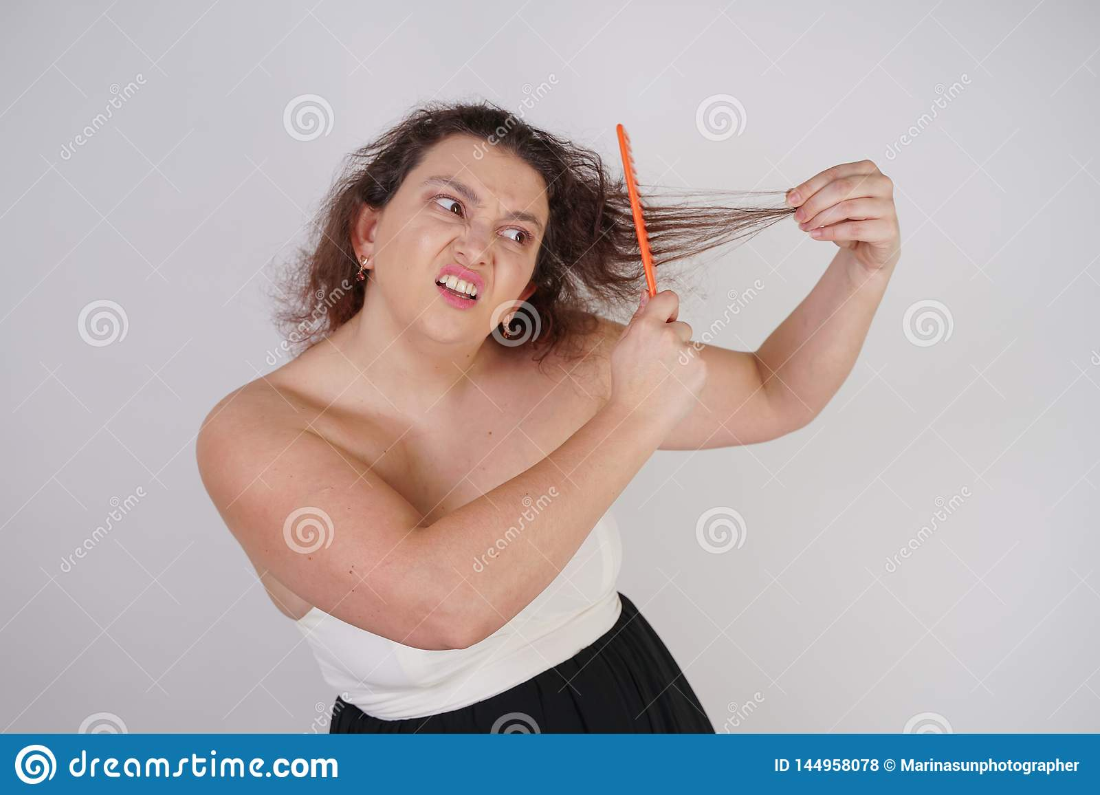 Emotional unhappy woman with disheveled hair tries to comb them and suffers. curvy girl stands on white background in Studio alone