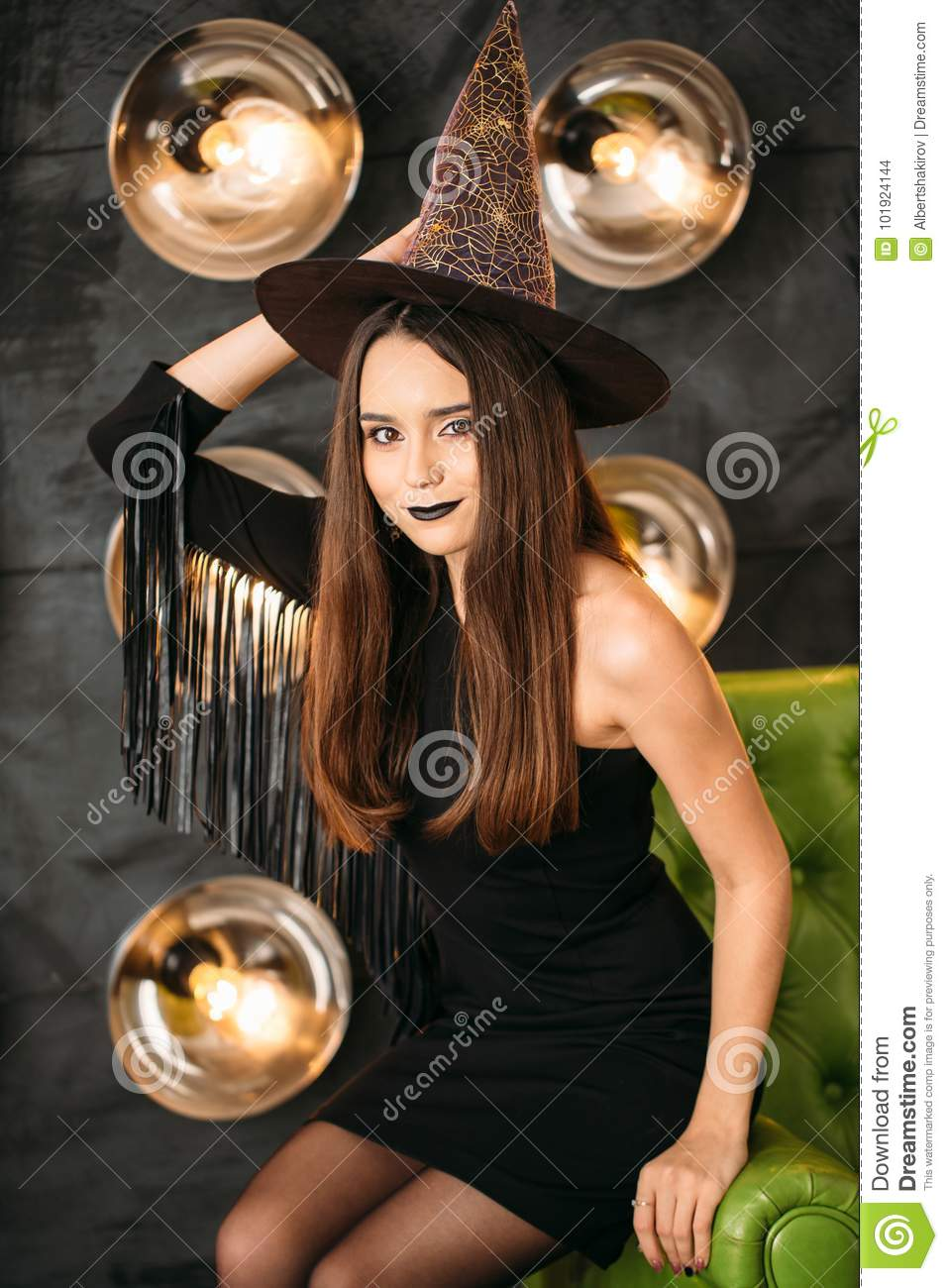 Happy gothic young woman in witch halloween costume with hat sitting at chair