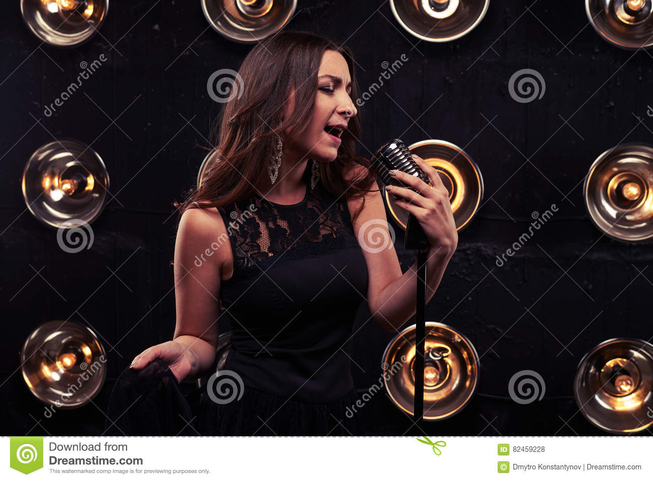 Emotional young woman holding a retro silver studio microphone i