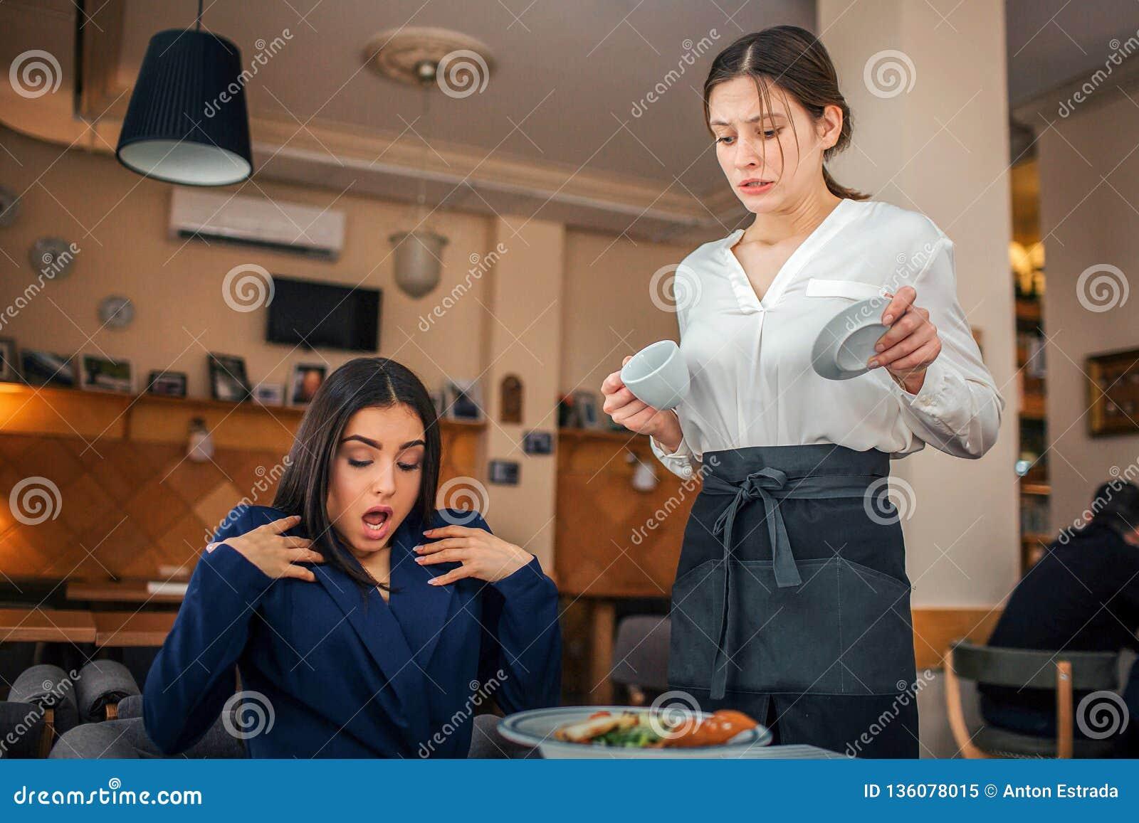 Emotionale junge Geschäftsfrau sitzen bei Tisch im Restaurant Sie wird überrascht und schaut unten Kellnerin gießen etwas Kaffee