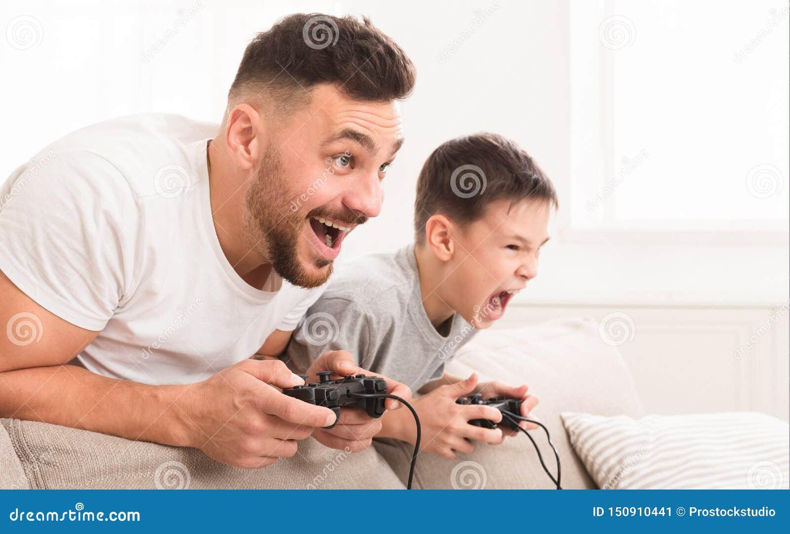 Emotioneel papa en zoons het spelen videospelletje die thuis, voor winst concurreren