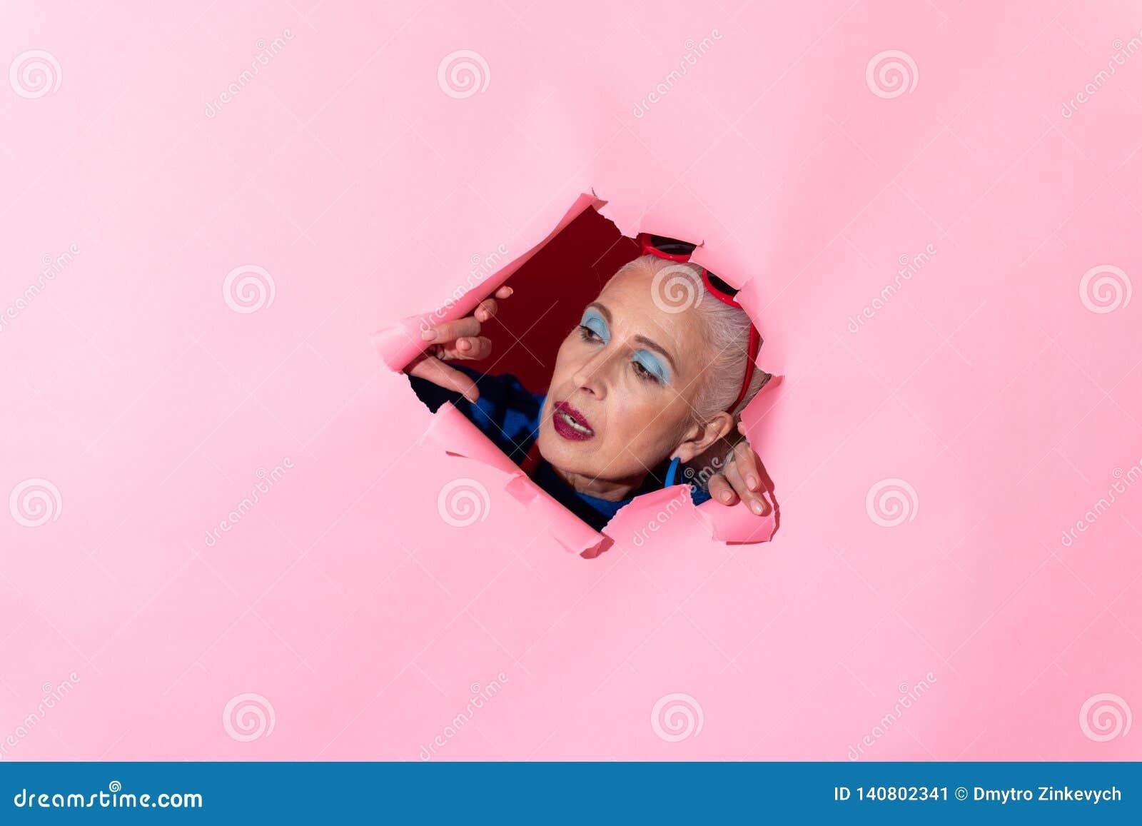 Emotioneel rijp model die roze document muur beschadigen